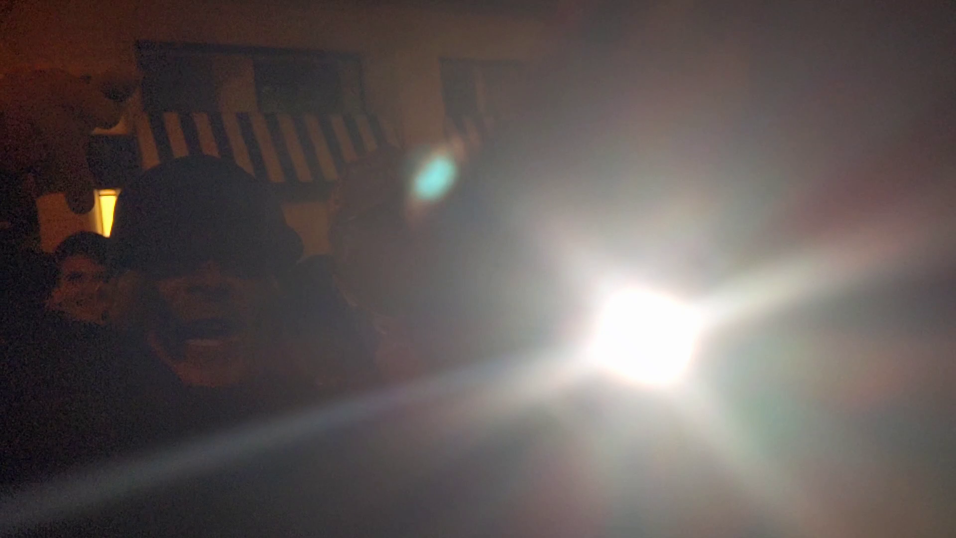 A bright light shines into the camera. In the dark background, a screaming man in a baseball cap is barely visible