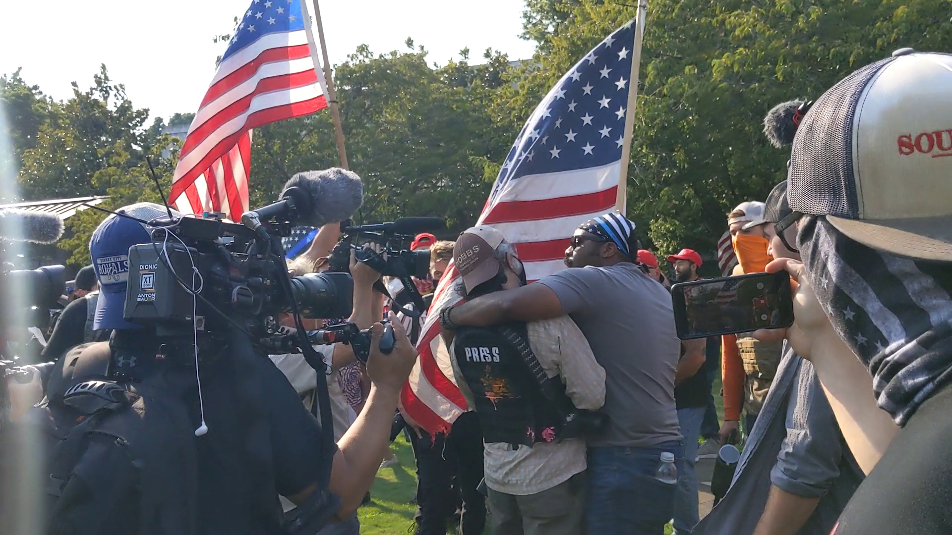 A black man in a Blue Lives Matter bandana embraces and shouts at a reporter visibly leaning back