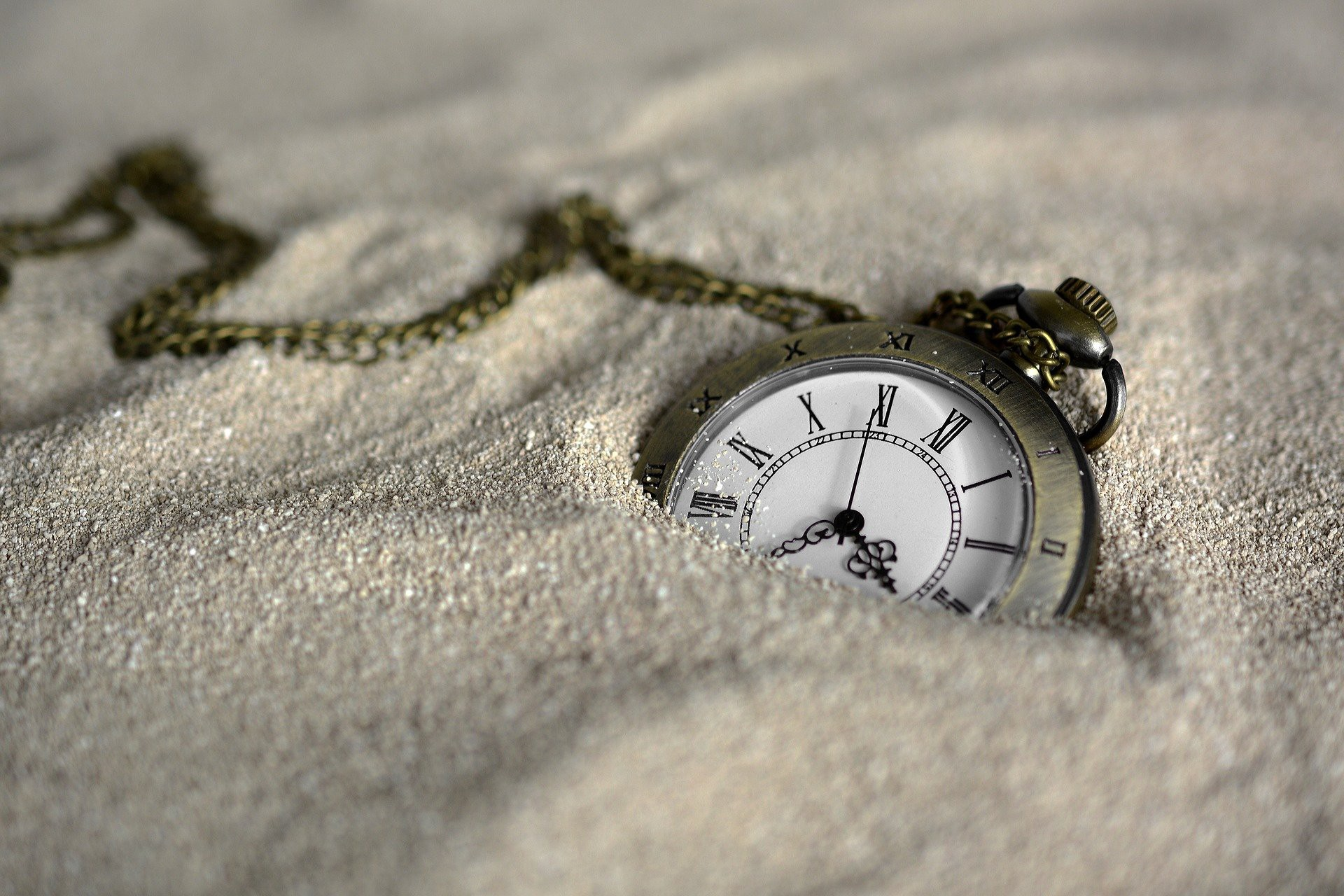 Old fashioned watch in sand