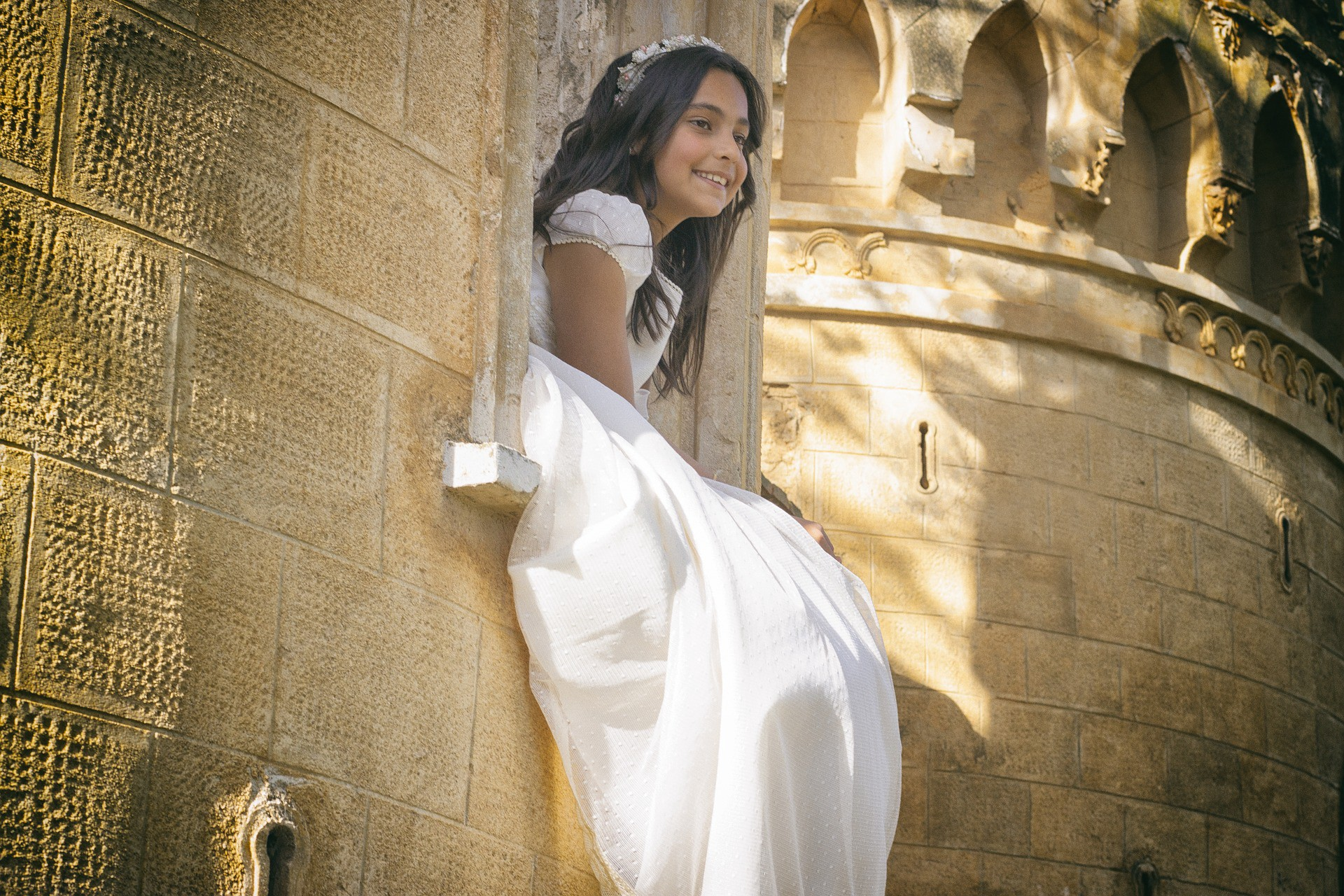 Pretty young girl in a white religious dress sitting in the window of an old cathedral and smiling into the sunlight