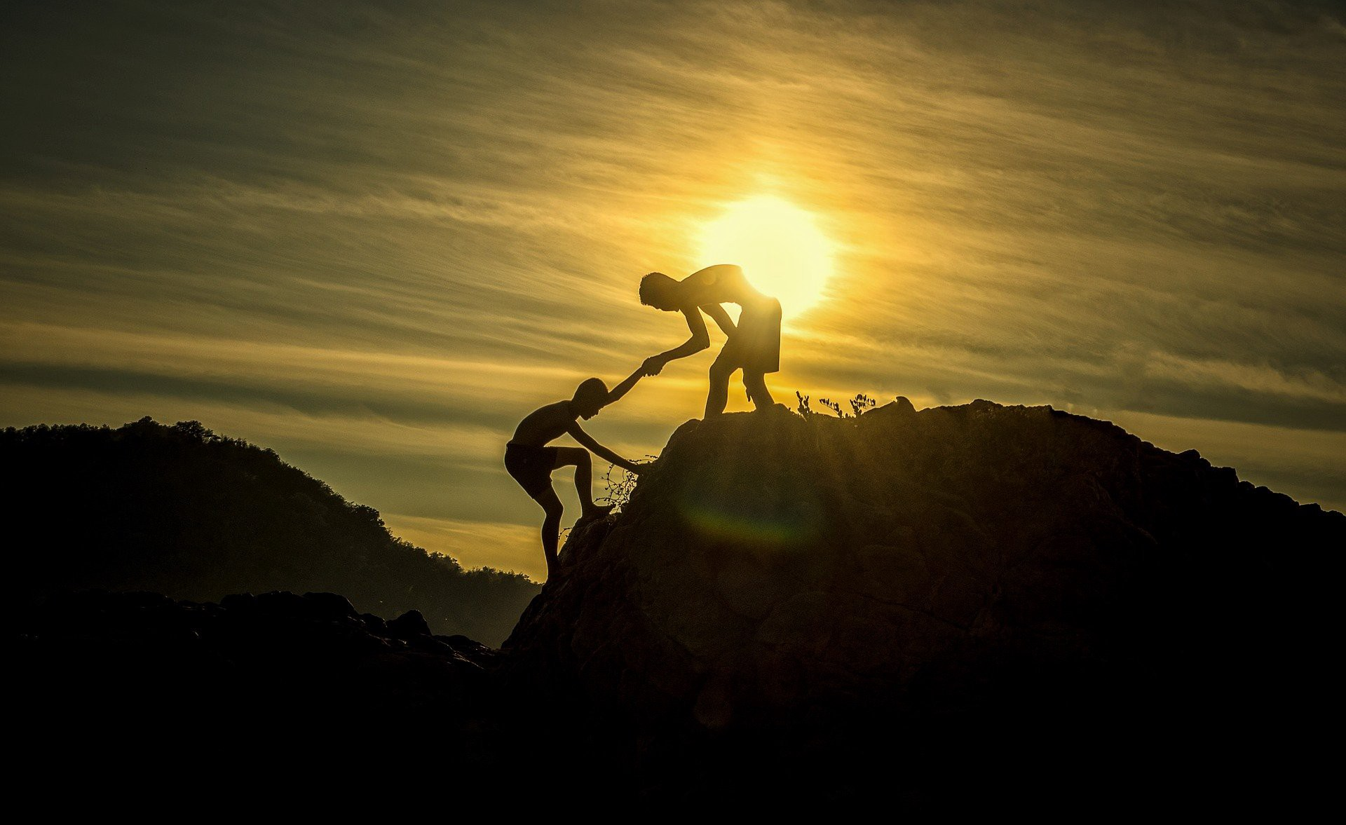 A silhouette of two boys on a mountain in front of the setting sun. One pulls the other up as he climbs.