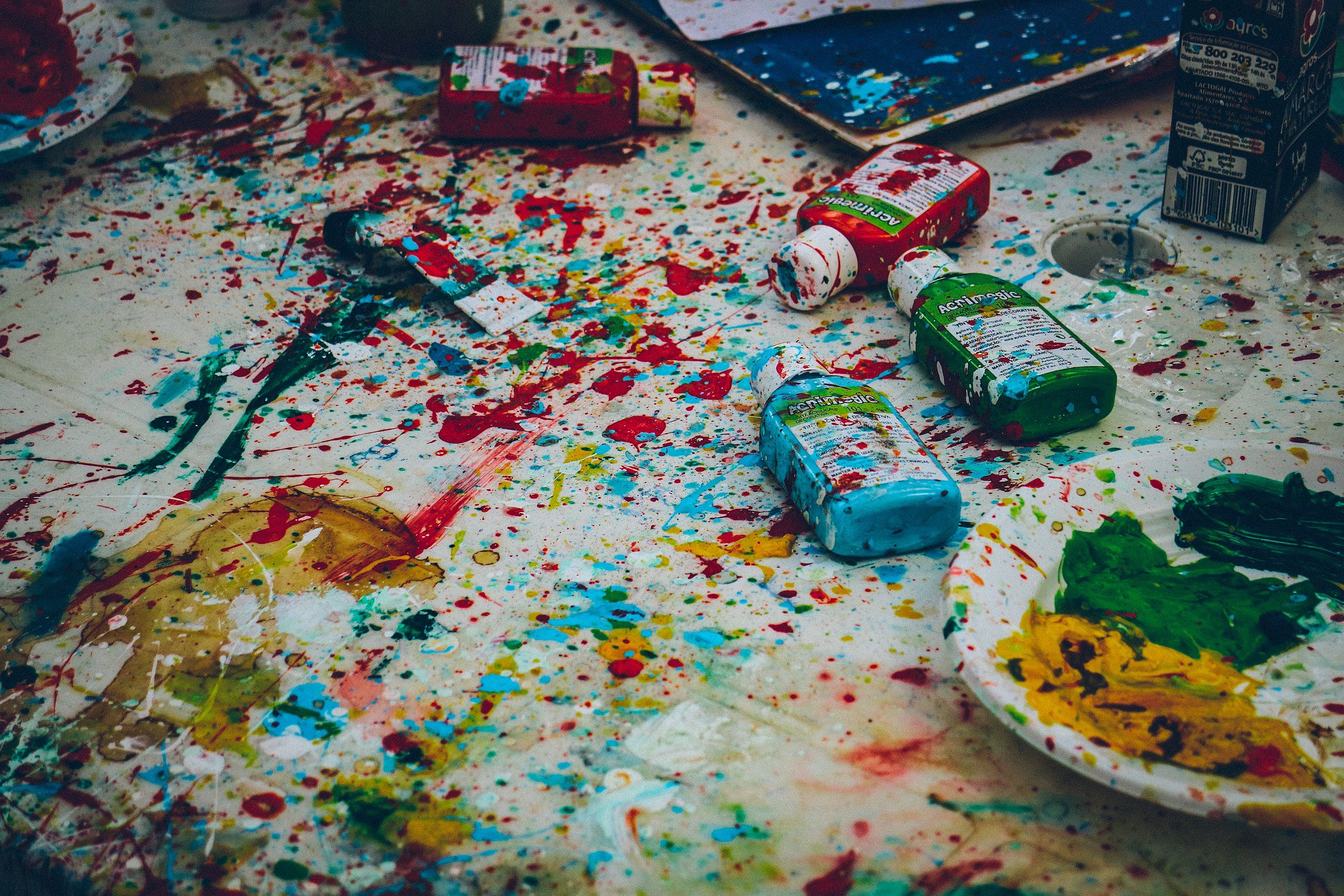 Splattered paints with a palette and art supplies.