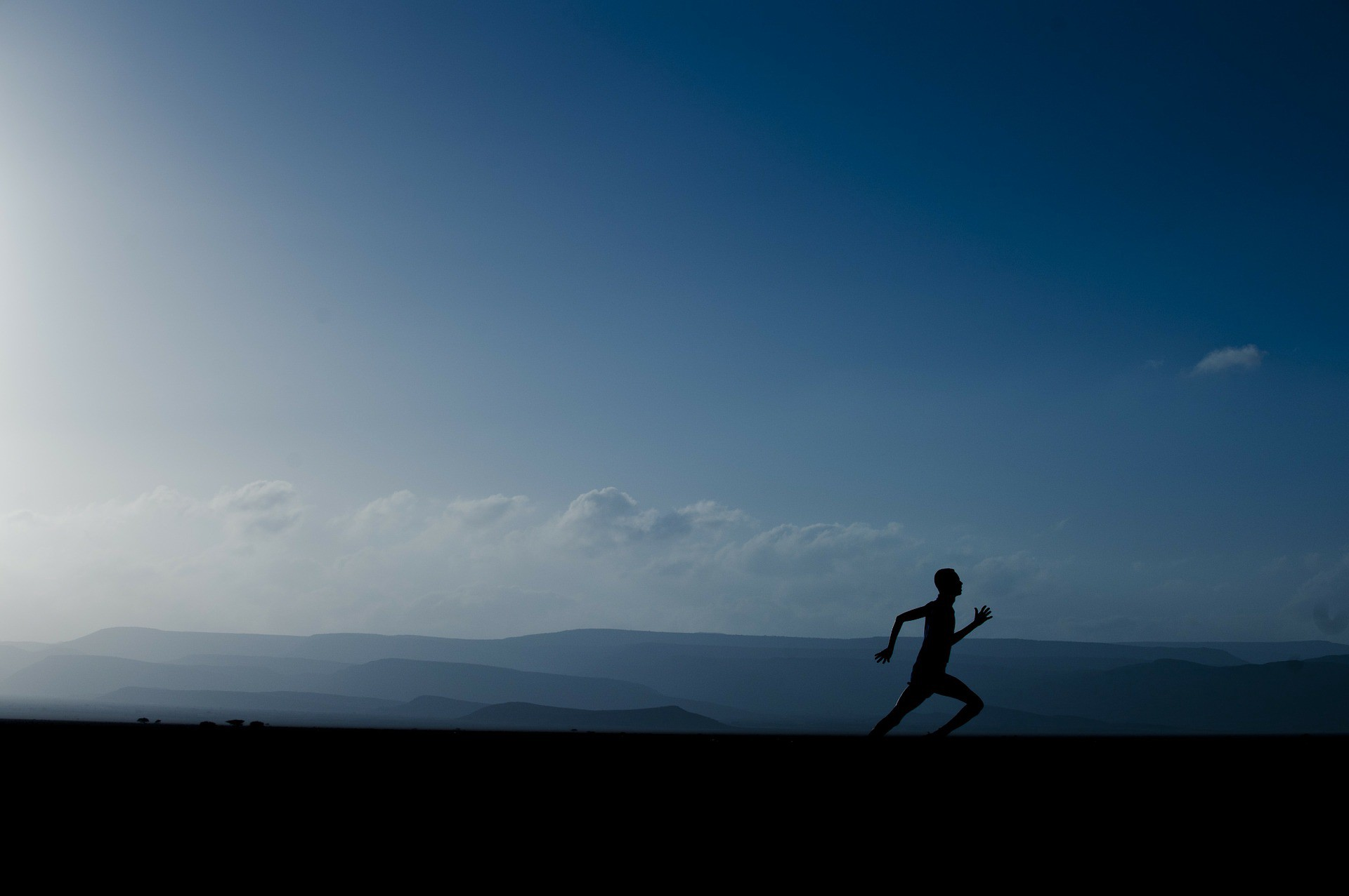 A person running in the evening against a big, blue evening sky.
