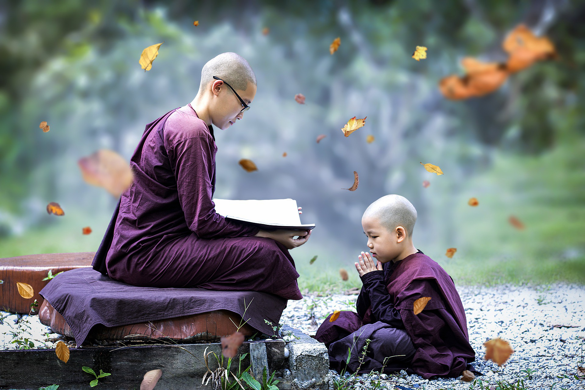 theraveda monk teaching a student who is sitting at his feet