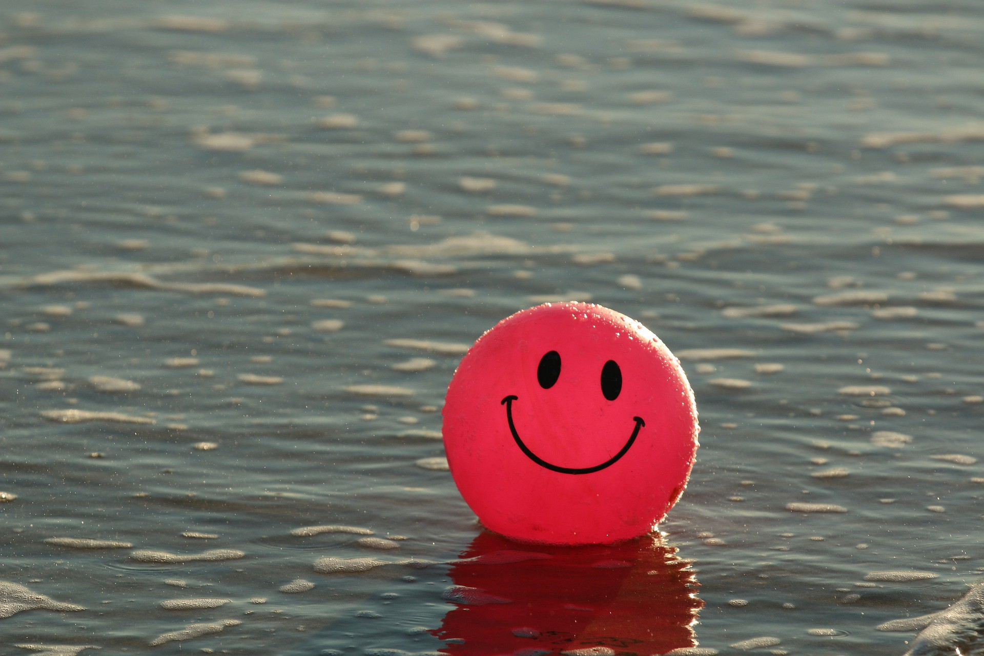 Baloon with a smiley face, floating on water