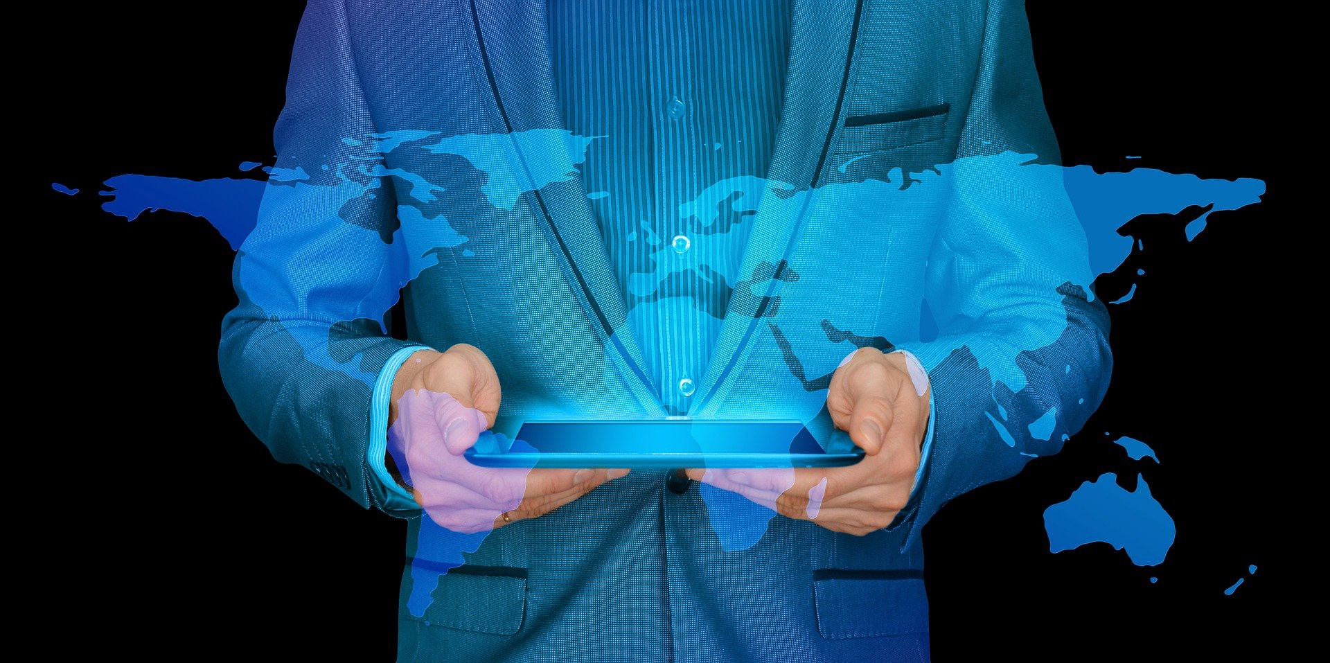 Man in a suit holding a digital tablet device, with a blue overlay of the contintents of the globe.