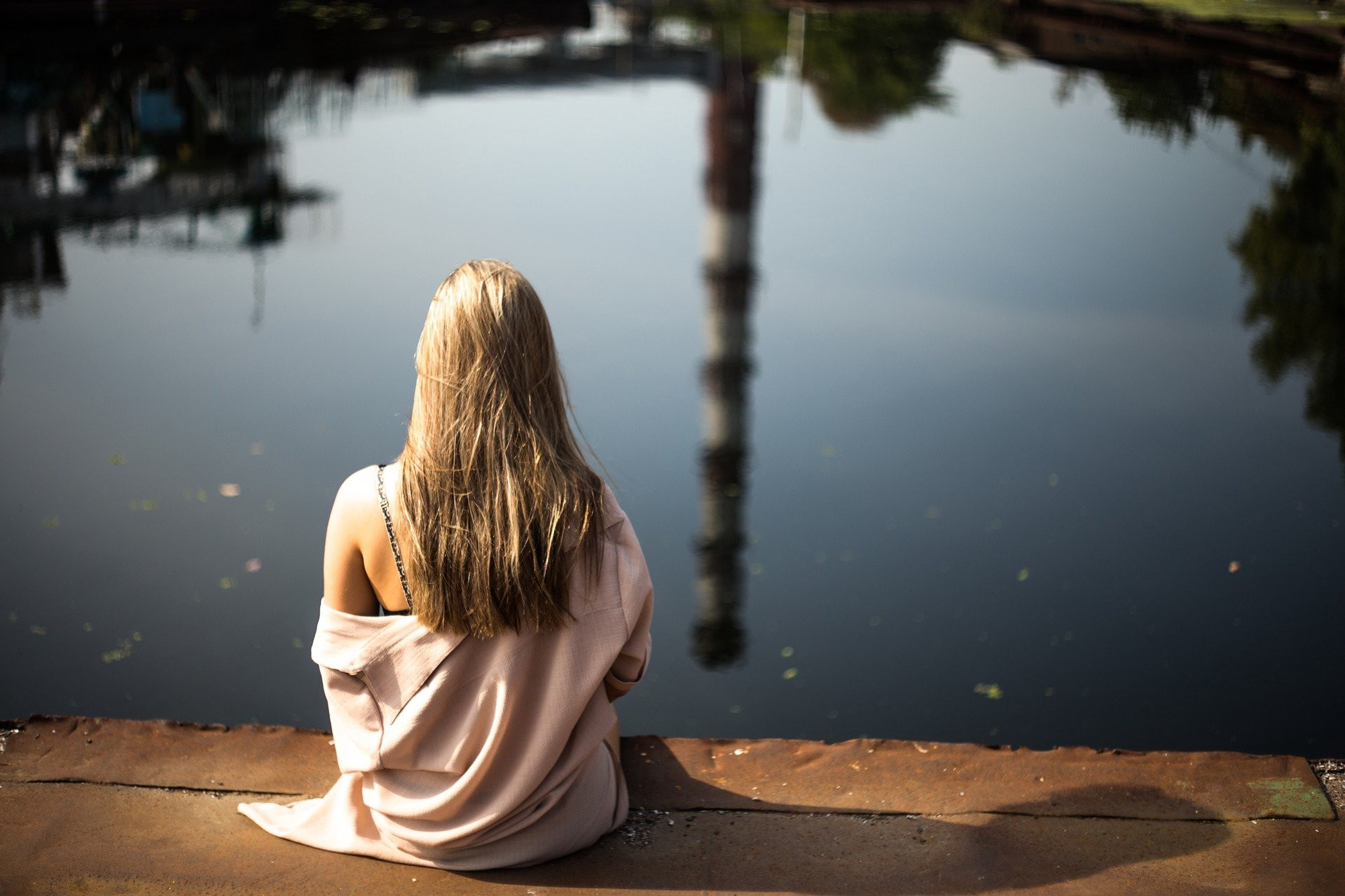 Blond Girl sitting on the side of a lake or pond, alone