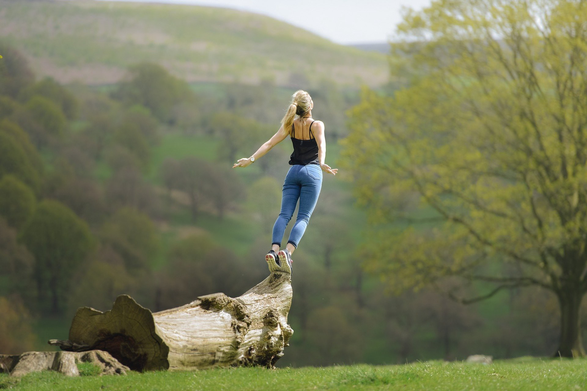 Woman jumping off the edge of a huge log