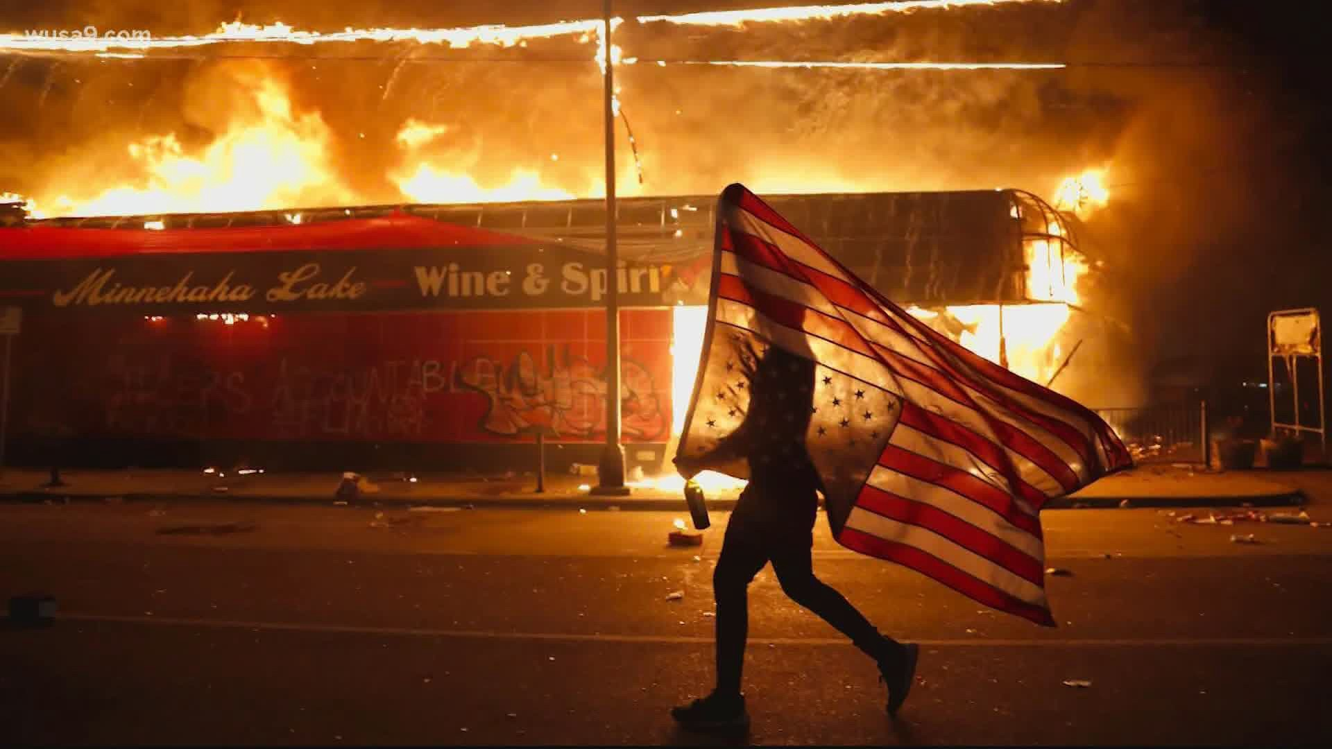 A protester carries an upside-down American flag past a burning liquor store in Minneapolis