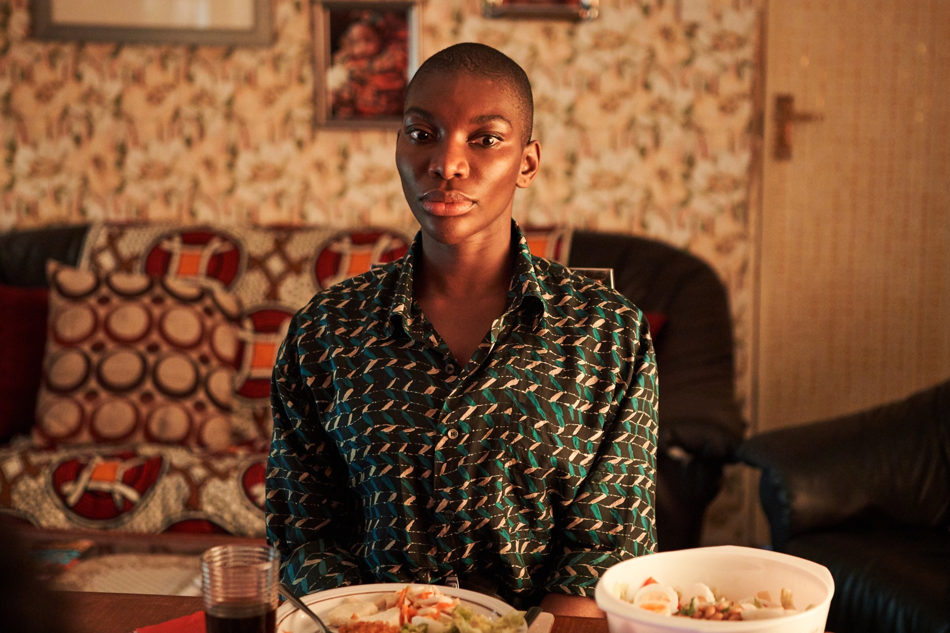 Arabella sitting at table in patterned shirt against patterned background.
