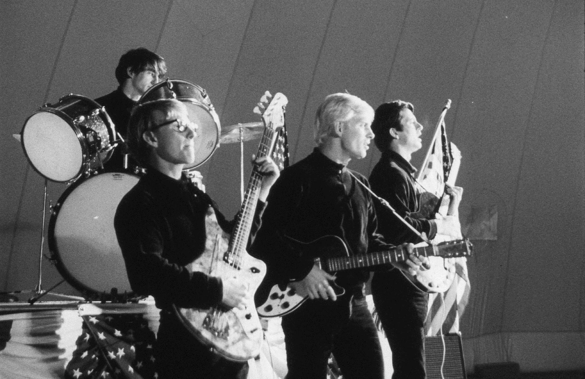 A rock band, comprised of four young men, is playing in the insides of the plastic dome.