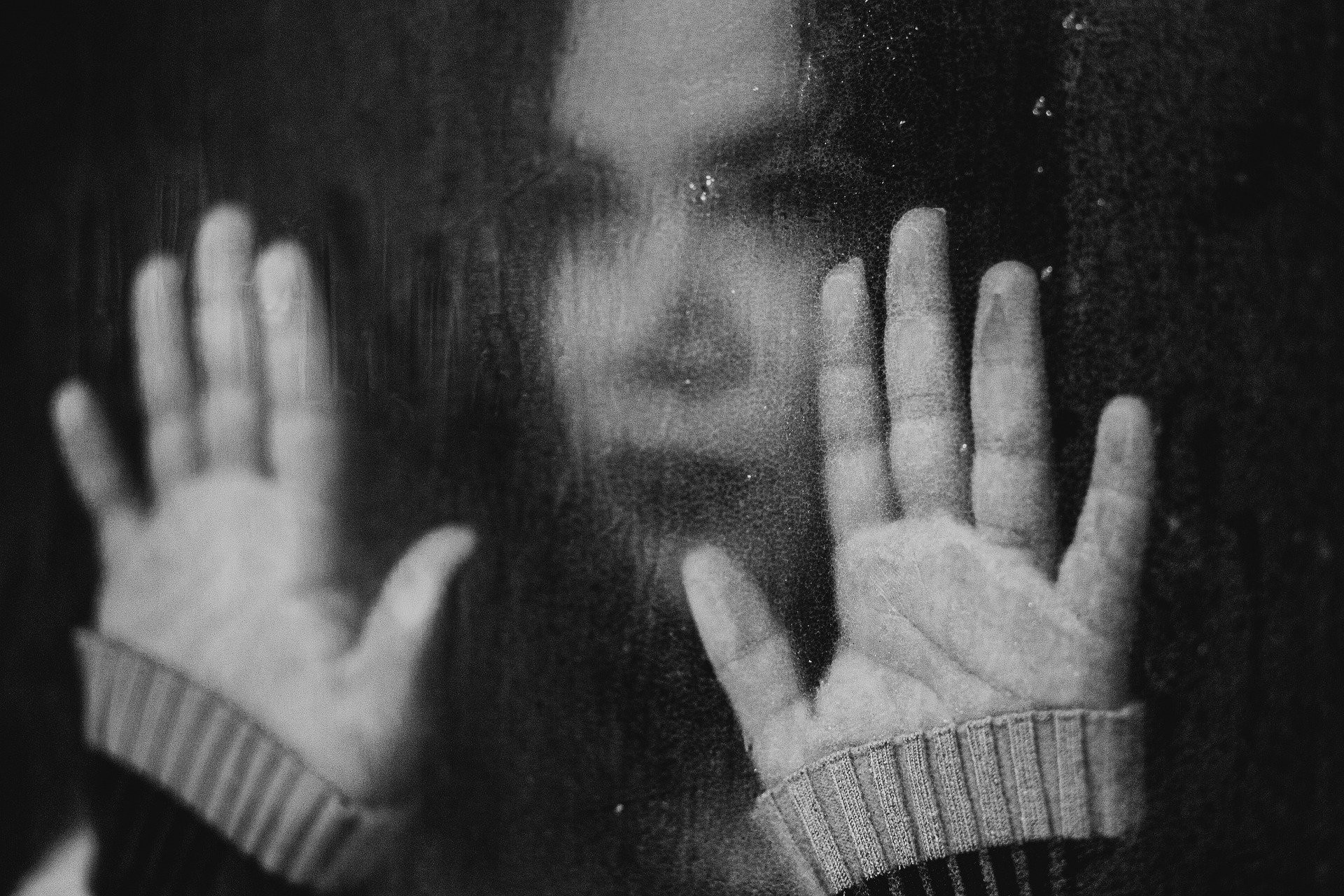 Black and white photo or a woman looking out a window with her hands pressed against the glass. It is raining outside.