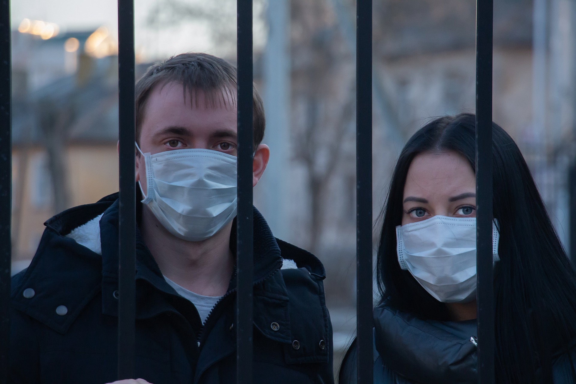 man and woman with face masks, behind prison bars
