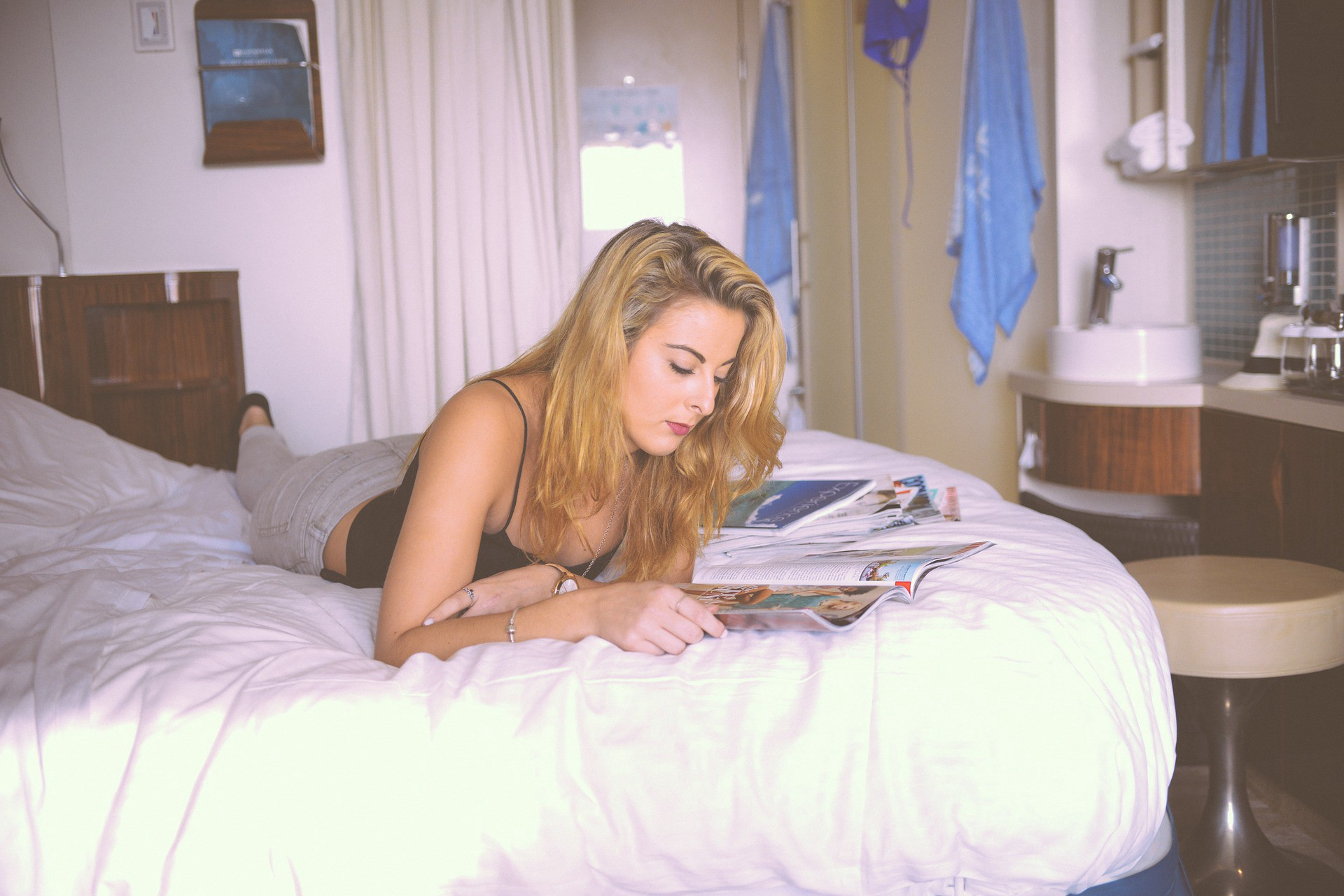 Woman lying on a bed reading a magazine. How to Write About What People Want to Read.