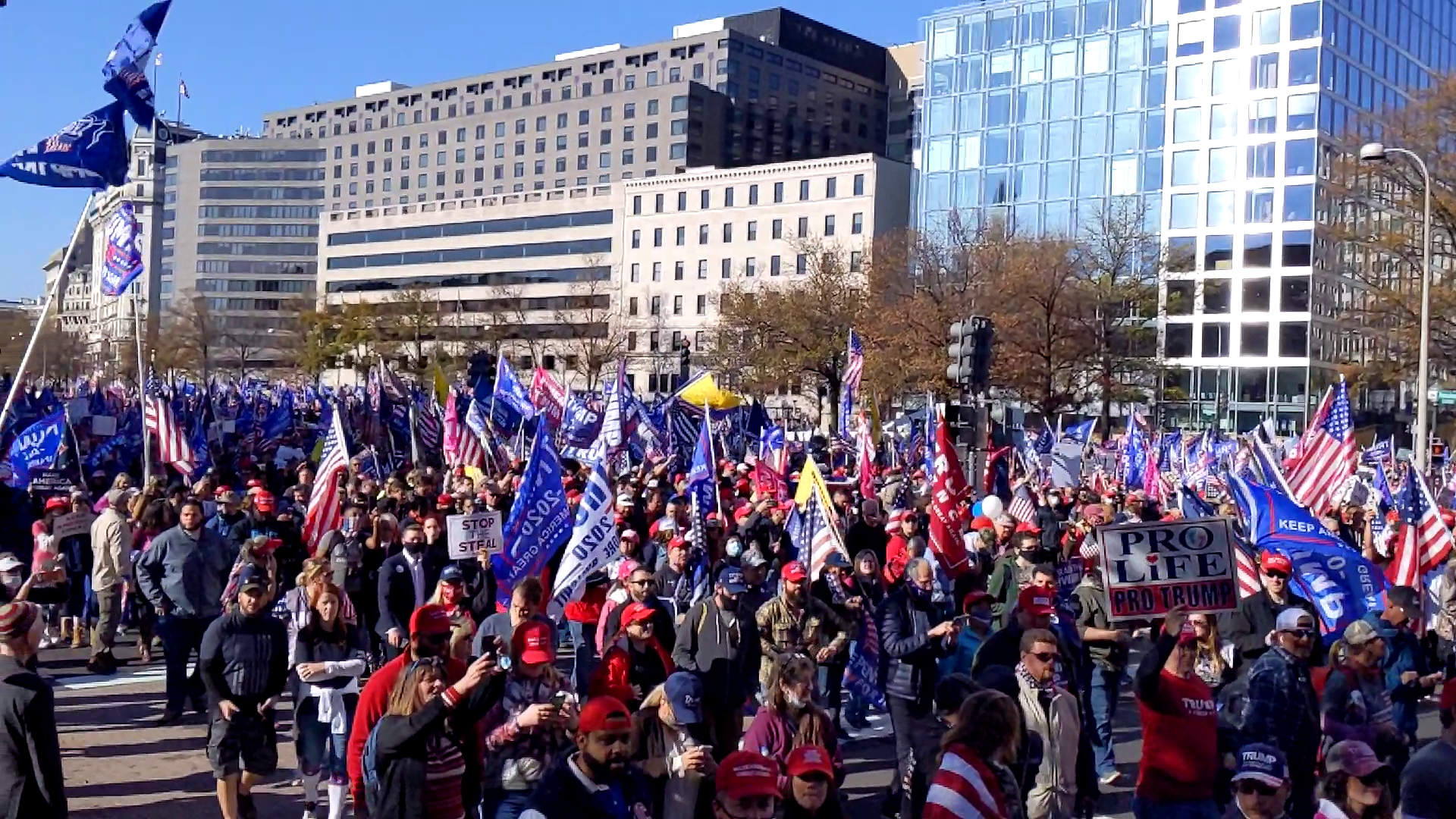 Thousands of Trump supporters carrying many Trump flags march down the streets of Washington DC