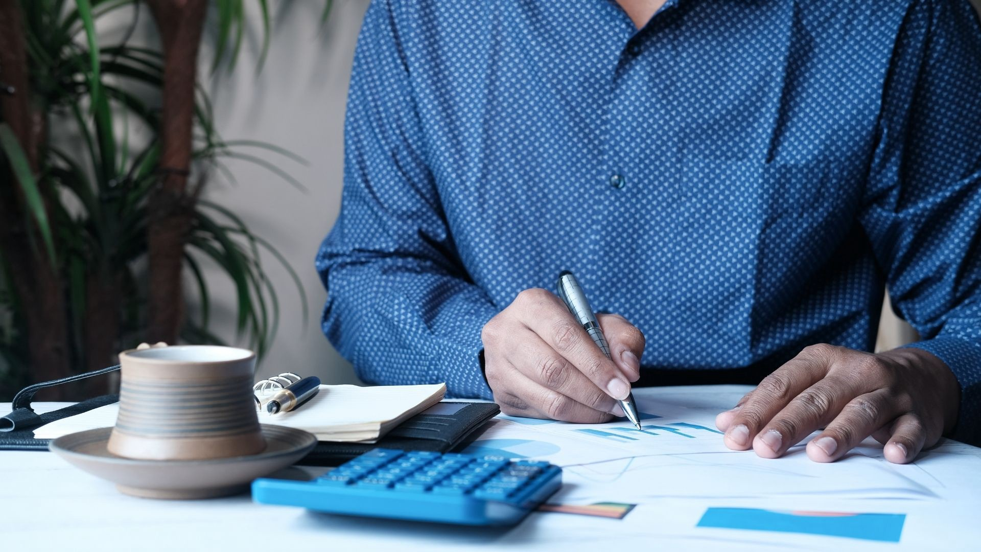 An individual in a blue shirt writing down a budget with a calculator, papers, and notebook in front of them