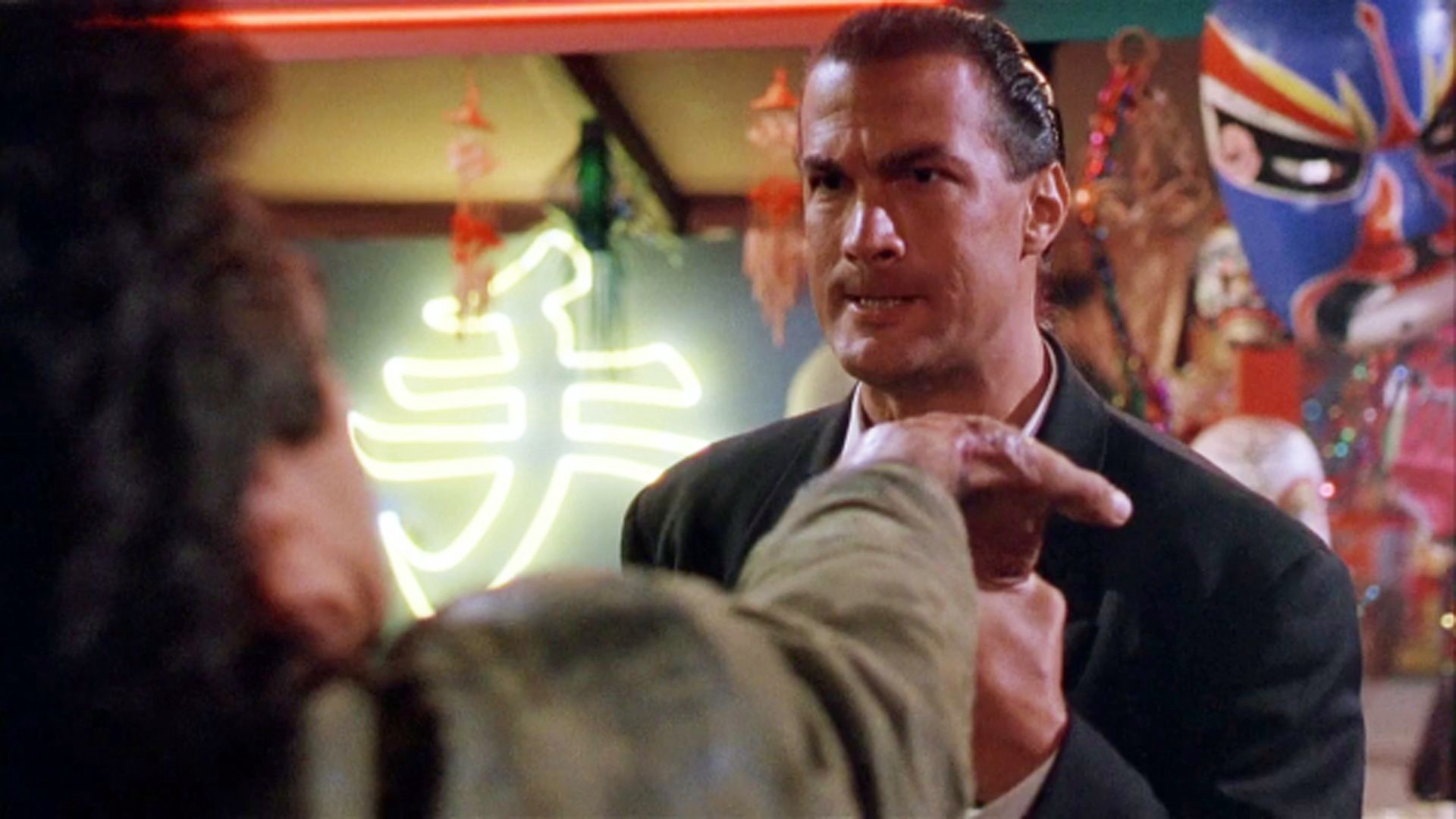 Mason Storm (Steven Seagal) glaring at a person whose hand he's yanked towards him palm-up.