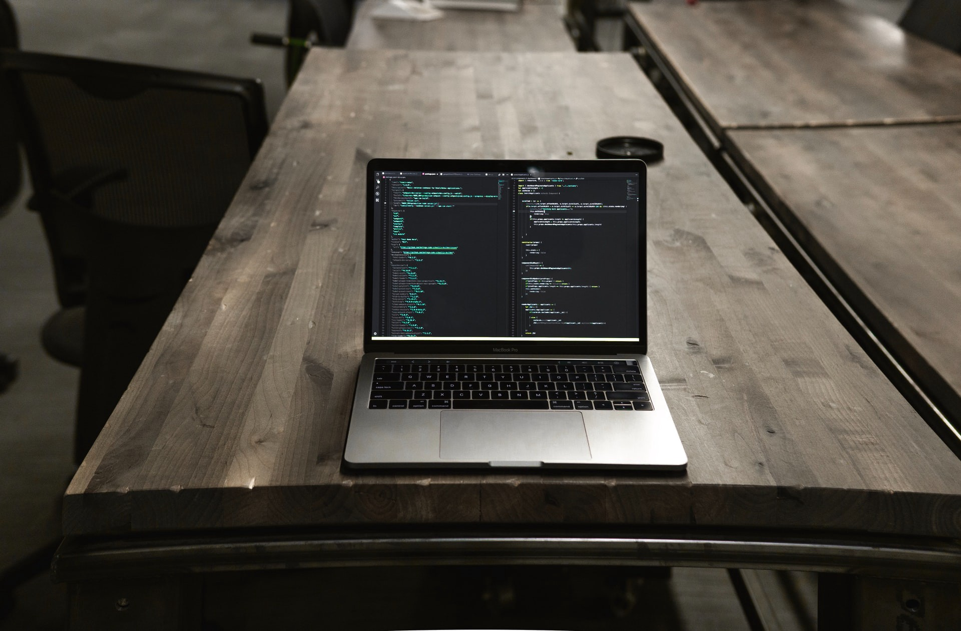 Laptop with code sits on an empty wooden desk