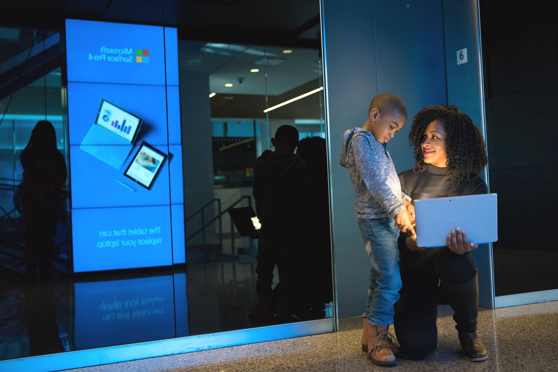 A woman and child looking at a laptop