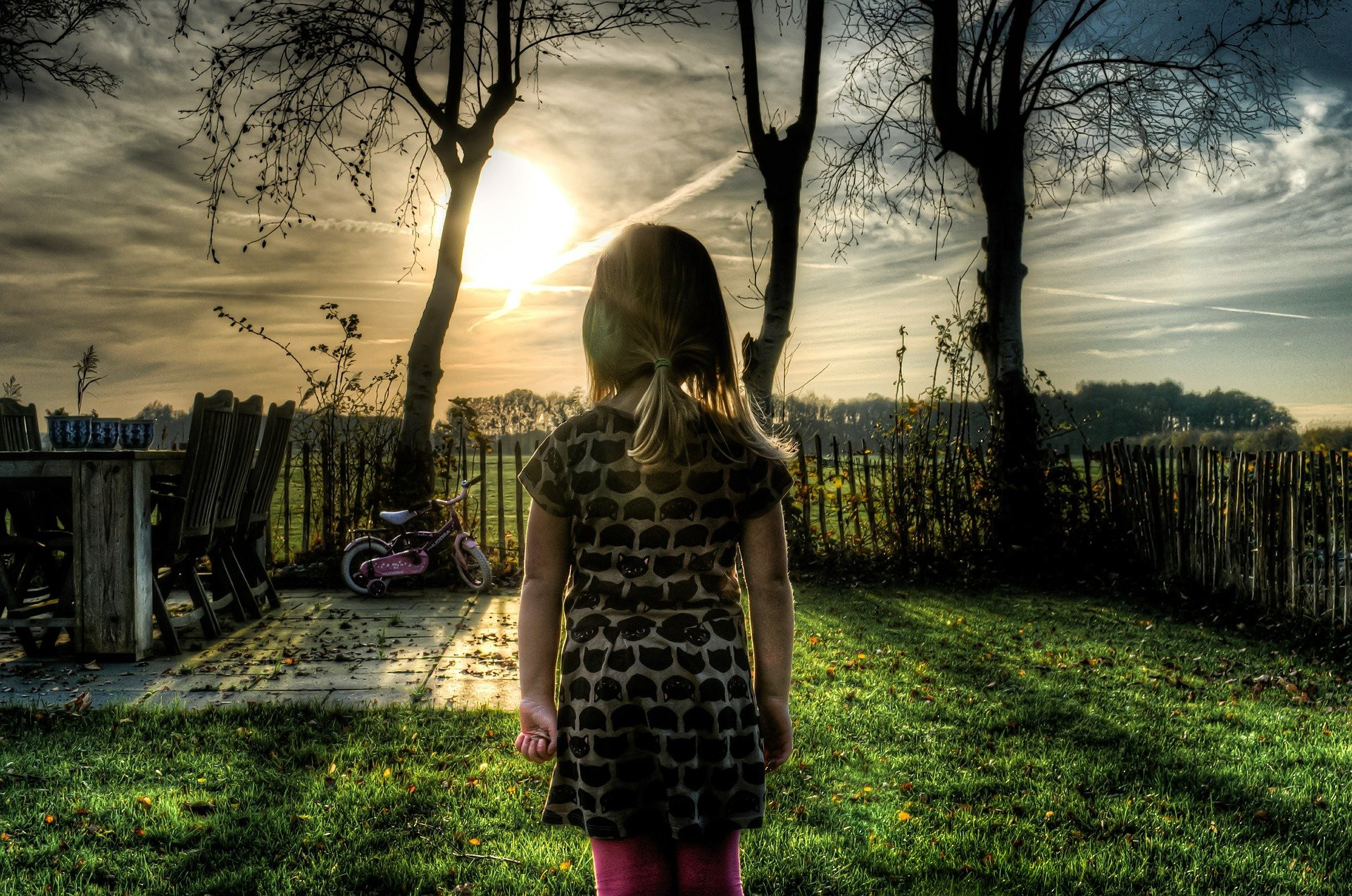Young child looking at an evening sunset, creepy photgraphs