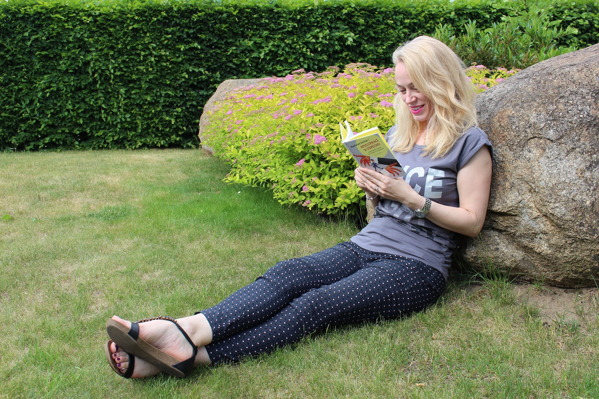 Woman sitting on the grass reading