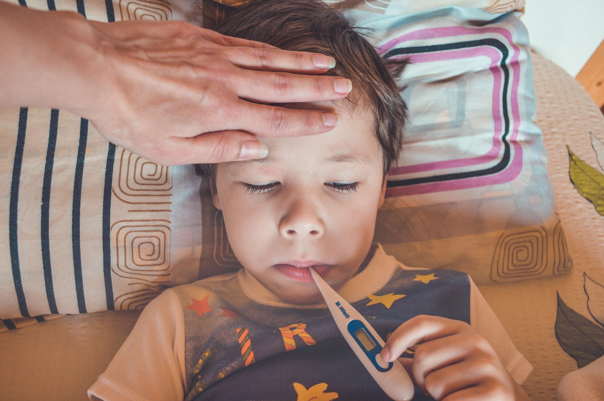 Child in bed with thermometer. Mom's hand on his forehead