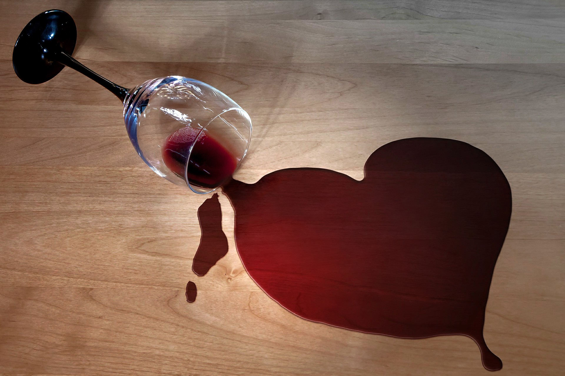 Spilled red wine into the shape of a heart