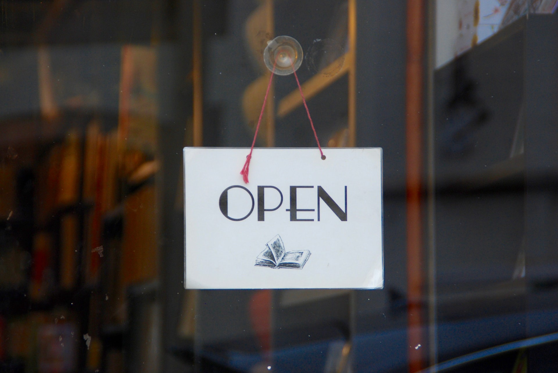 A sign on the door signifying the store as open to customers.