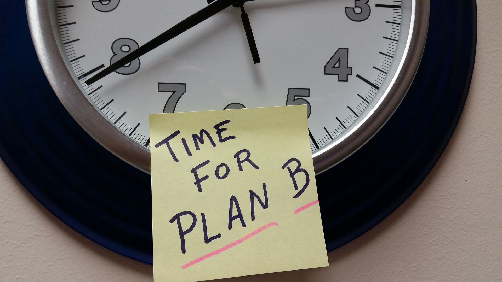 """An analog clock with a sticky note saying """"Time For Plan B"""""""
