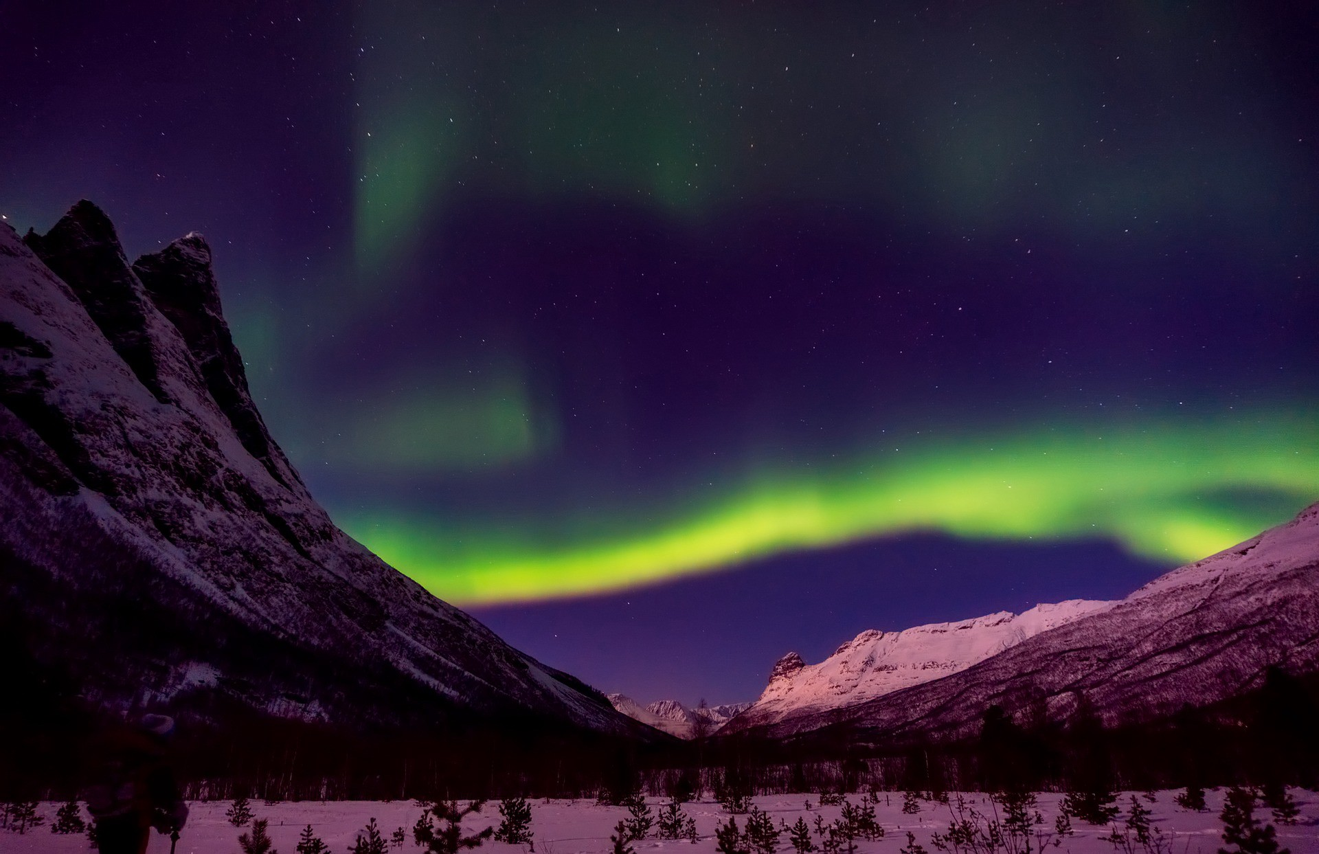 A view through a mountain valley of the northern lights, lighting the sky with a spectrum of colors