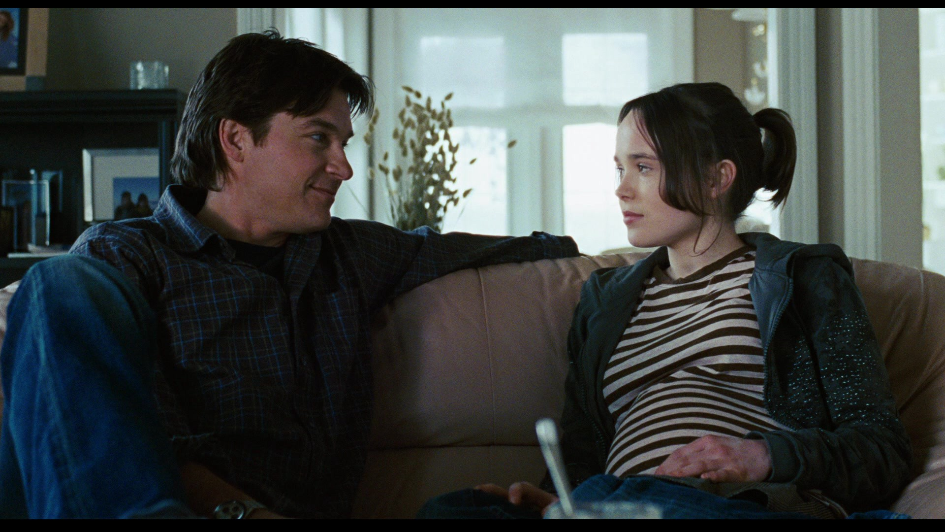 Jason Bateman as Mark Loring and Elliot Page as Juno MacGuff sitting on a couch, looking at each other.