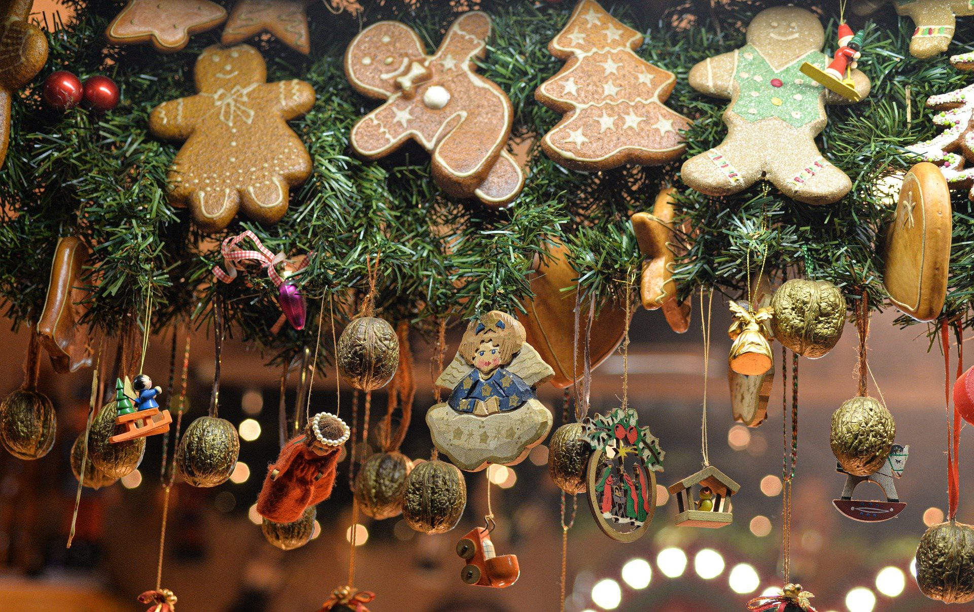 A bunch of Christmas decorations and gingerbread men are hanging in the air, onto a birghtly lit background.