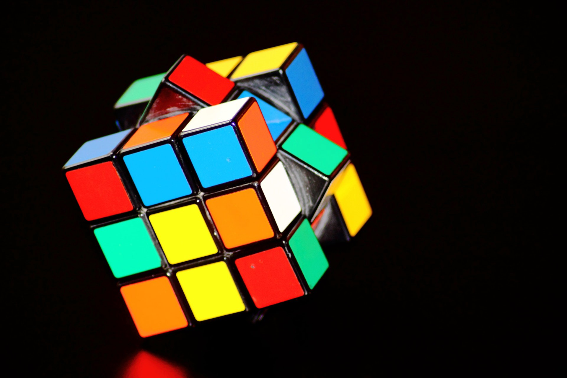 A Rubik's cube in front of a black background