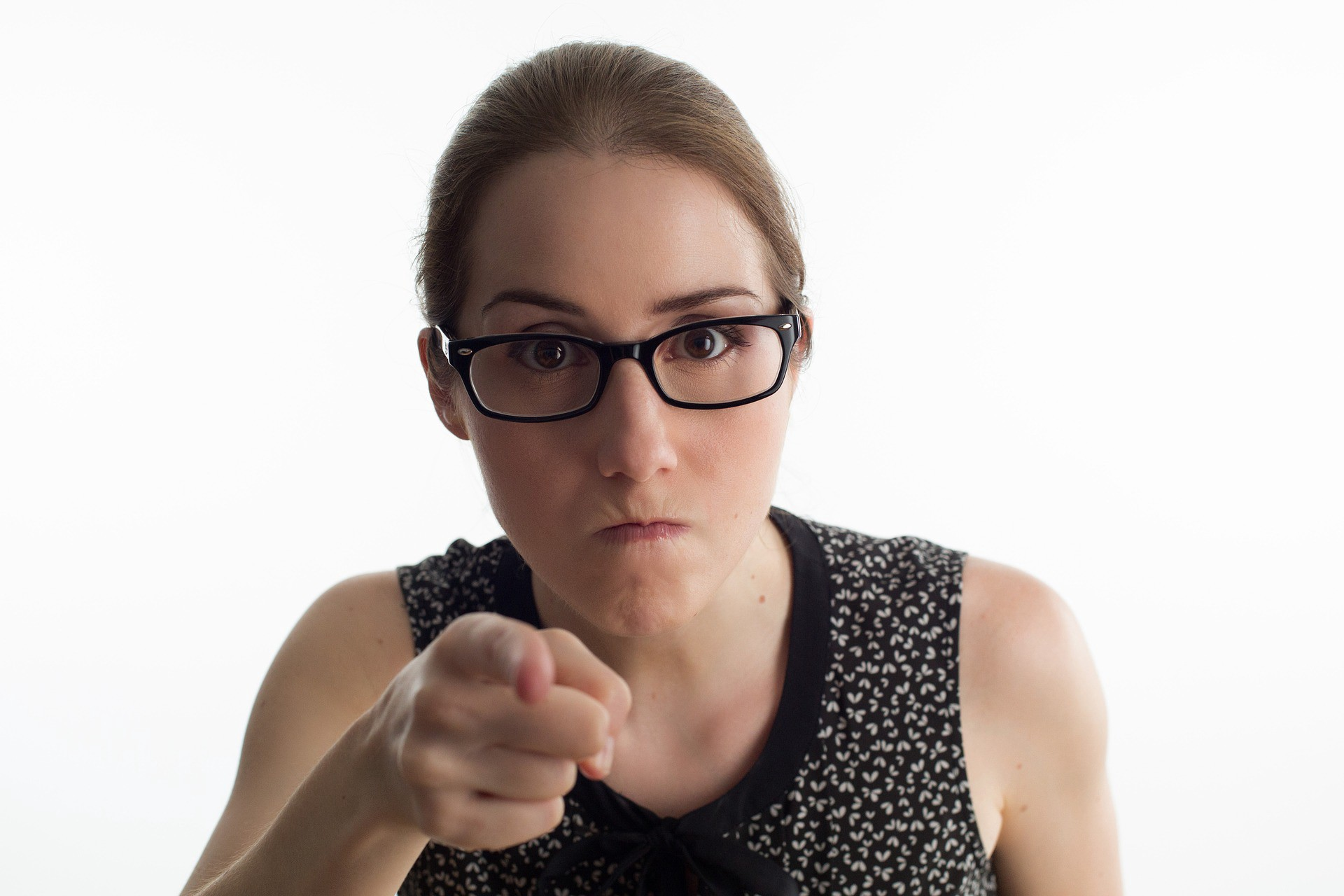 Angry young woman with her hair pulled back pointing her finger at the camera