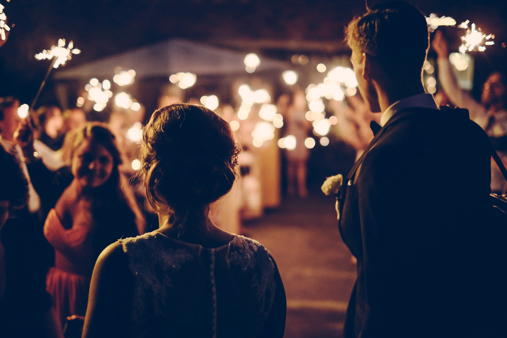 Bride and groom walking down the aisle to guests holding sparklers