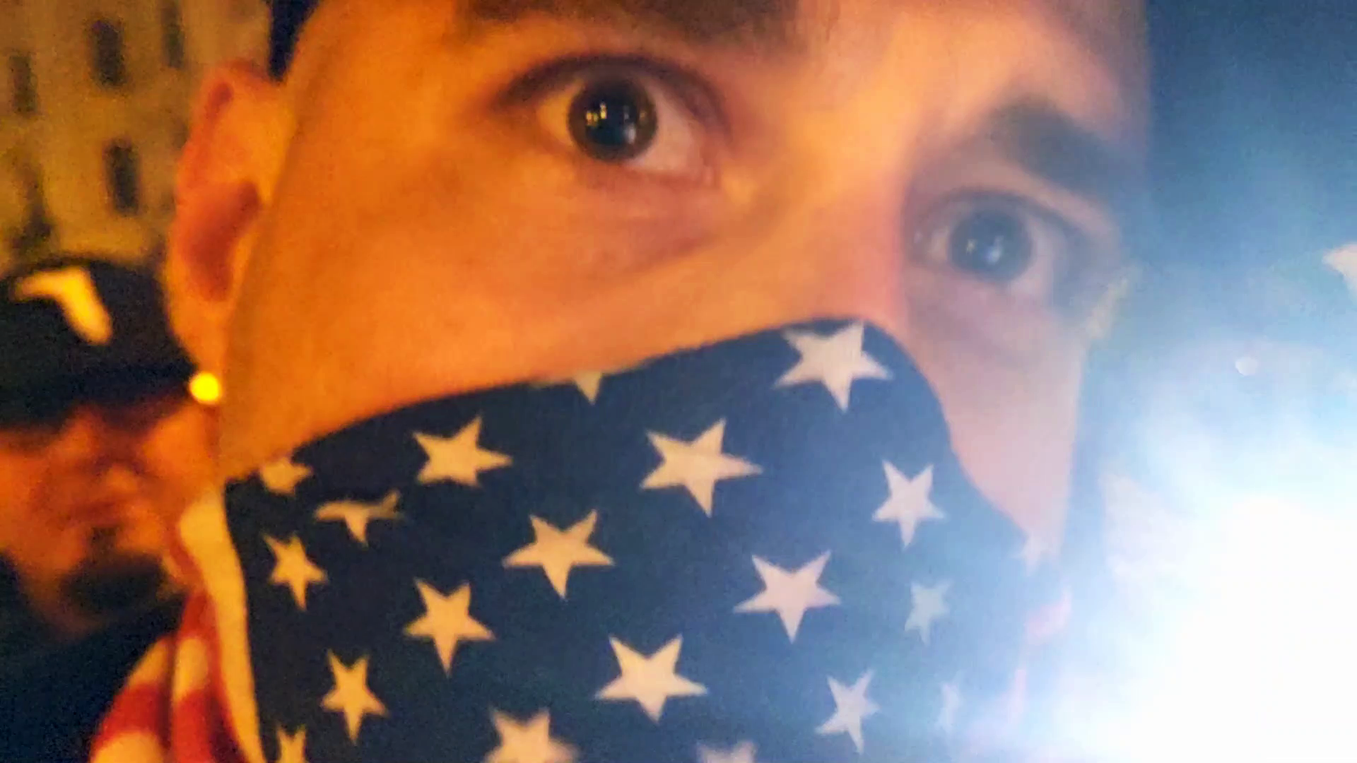 A man with an American Flag mask covering the lower half of his face looms uncomfortably close to the camera. He looks angry