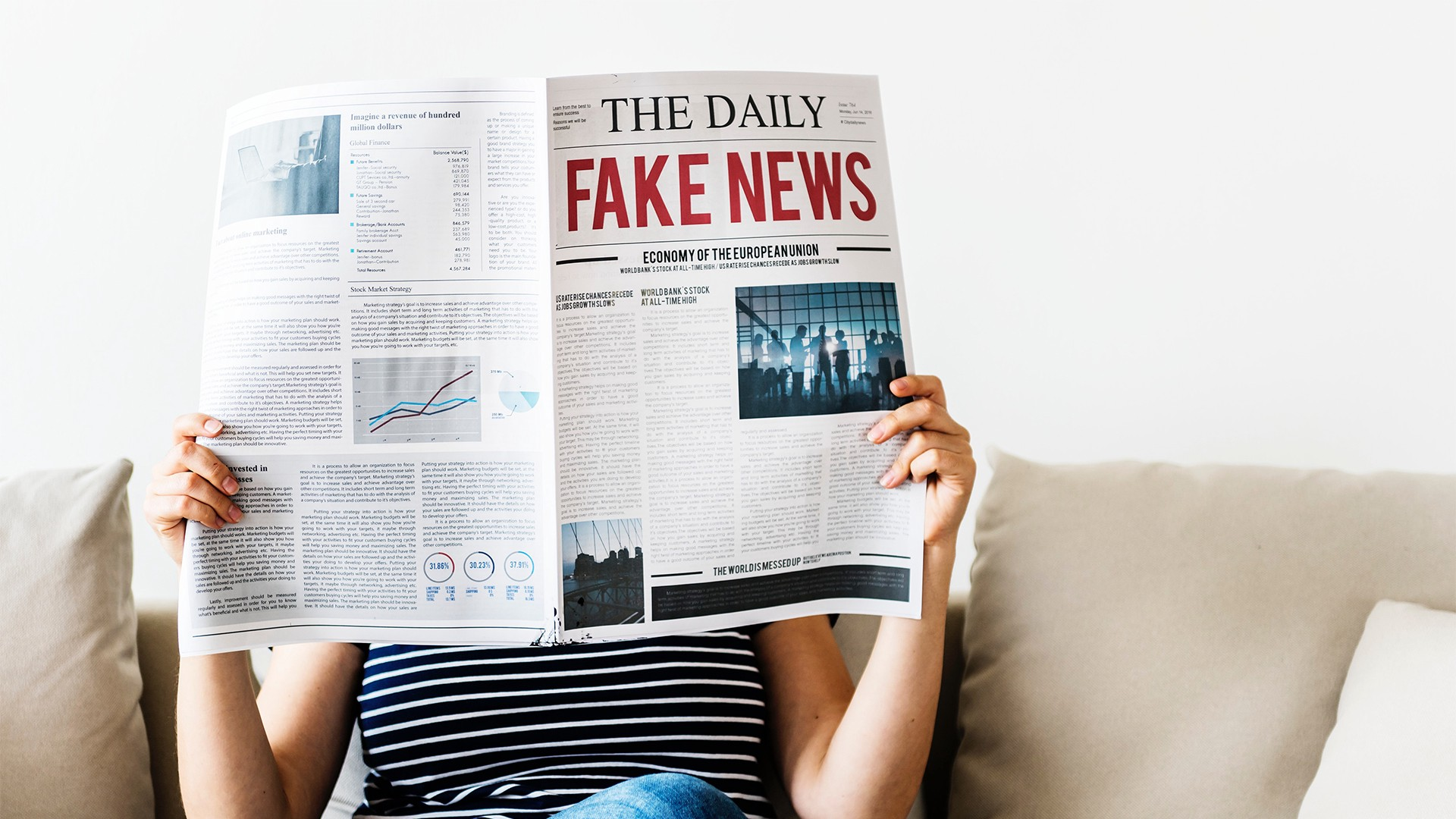 Woman sitting reading a newspaper with 'Fake News' in large bold print as the headline of the day.