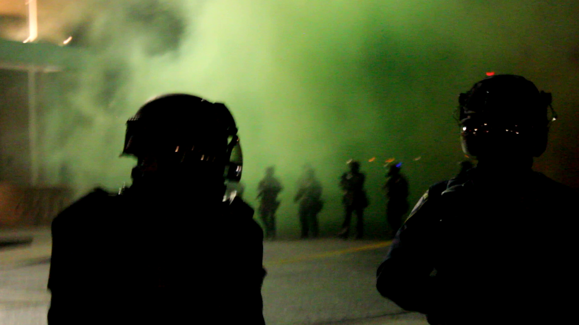 Two police officers in riot gear, with green smoke and a line of riot cops in the background
