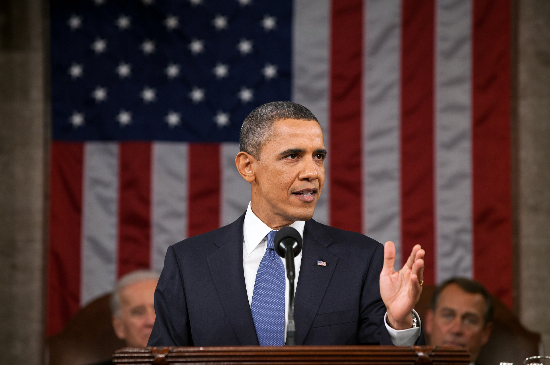Former President Obama delivers a speech with the American flag in the background.