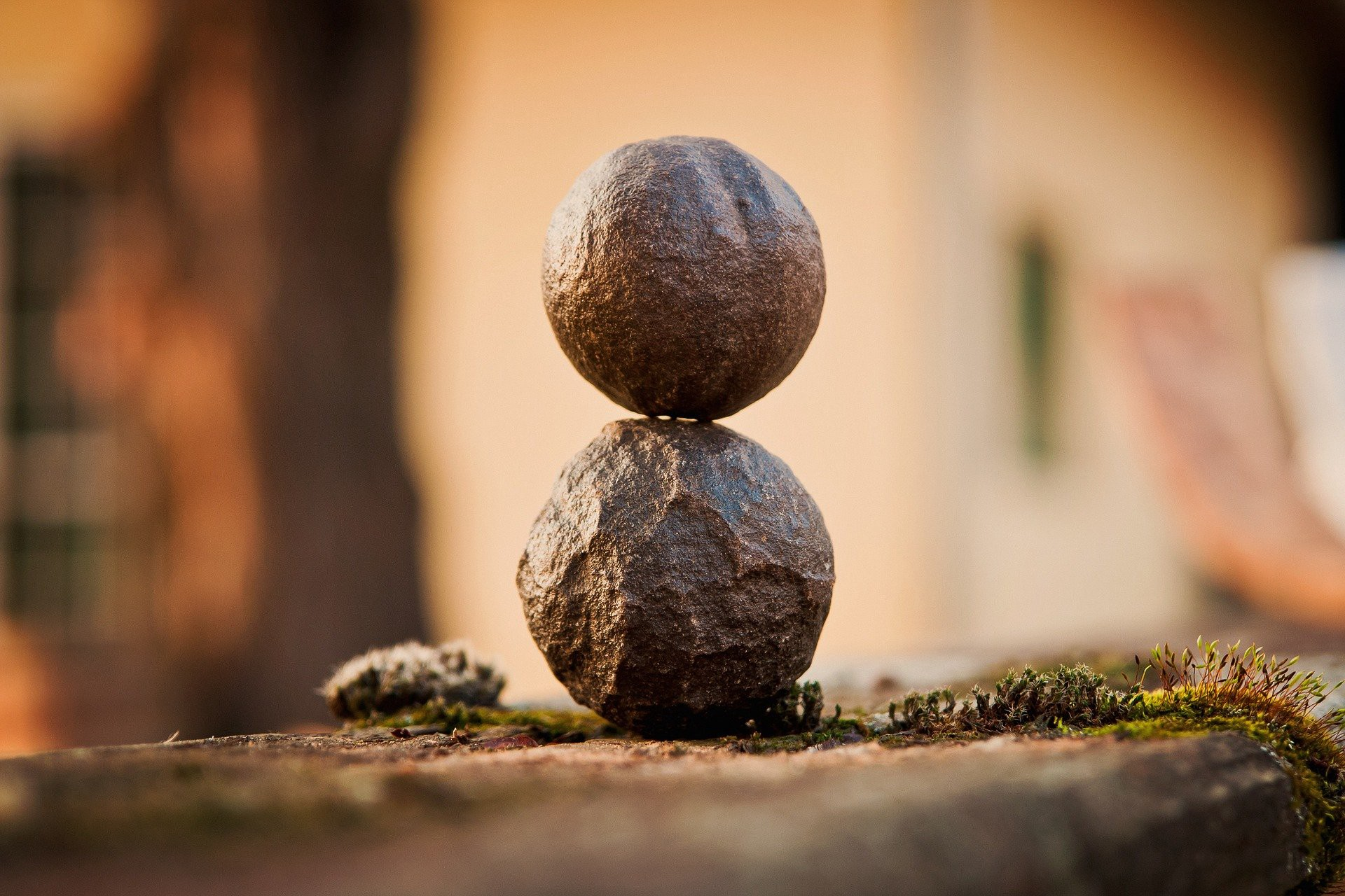 Serene photo of two spherical rocks resting on top of each other, with a warm orange-brown background and some moss.