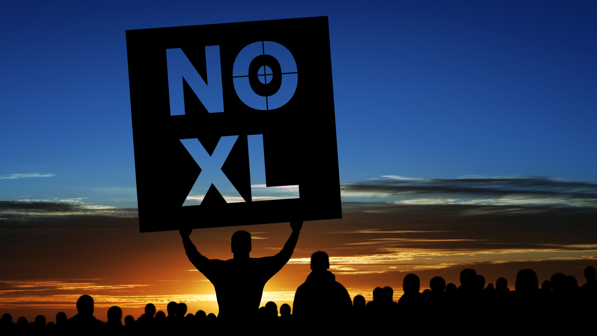 """Protestors at sundown. One protestor holds a sign that says """"No XL"""", referring to the Keystone Pipeline Expansion"""