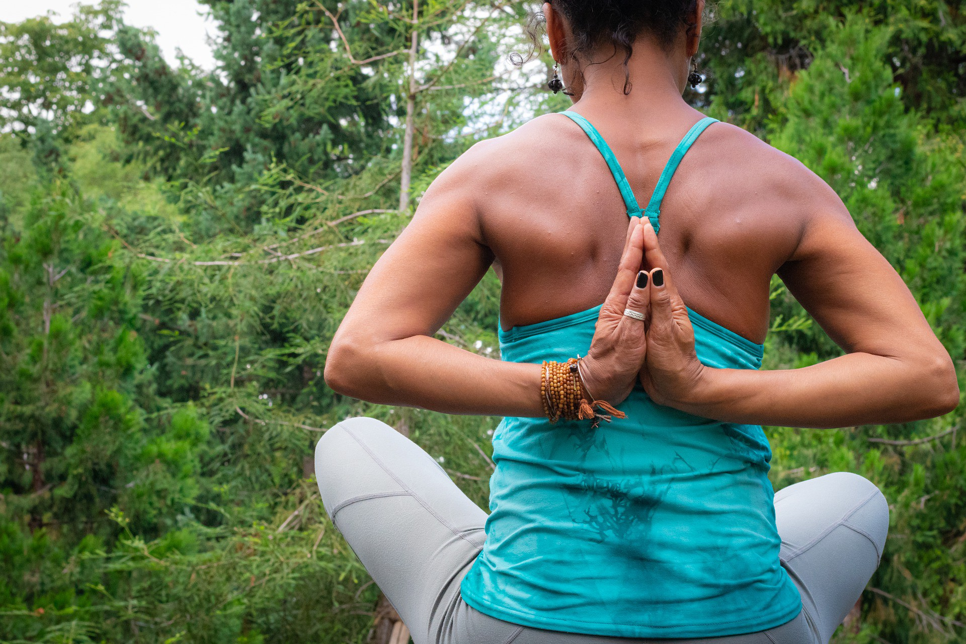 A woman practices yoga outside to help fight weight gain as she gets older. We see her from the back and her hands are behind her in prayer position. She is wearing a blue tank top and gray leggings.