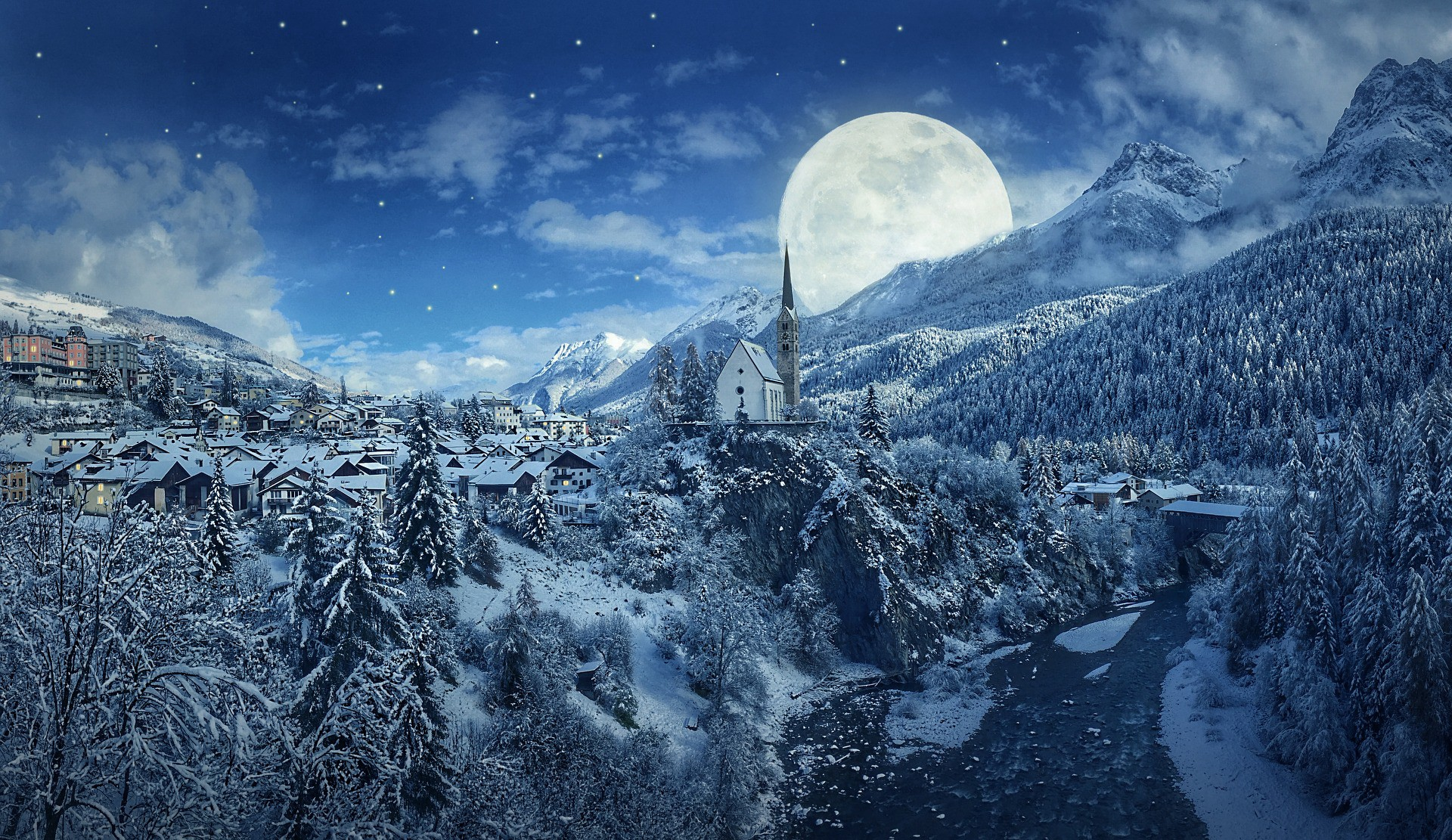 Full Snow Moon rising above white mountains and a village.