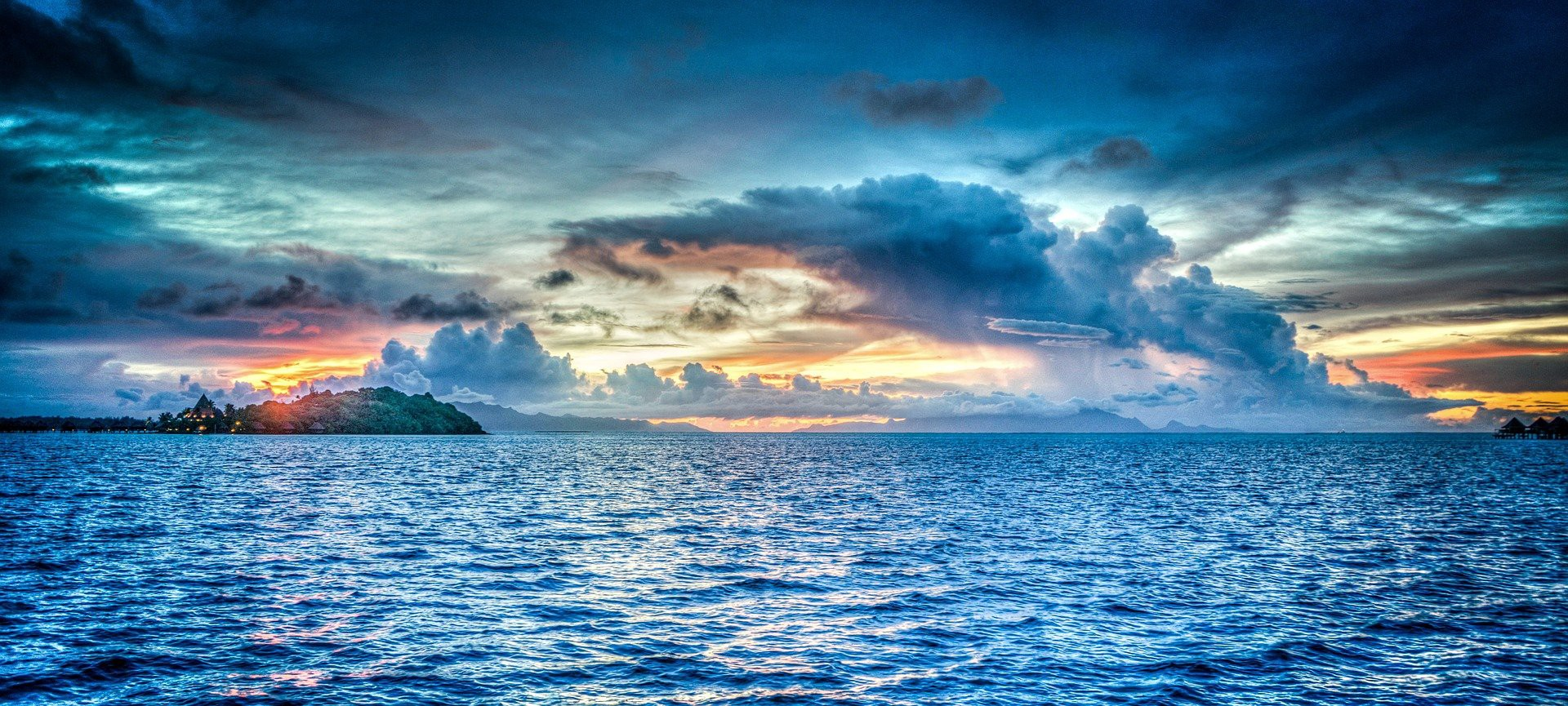 Blue sky with a hazy sunset above glistening coral blue sea
