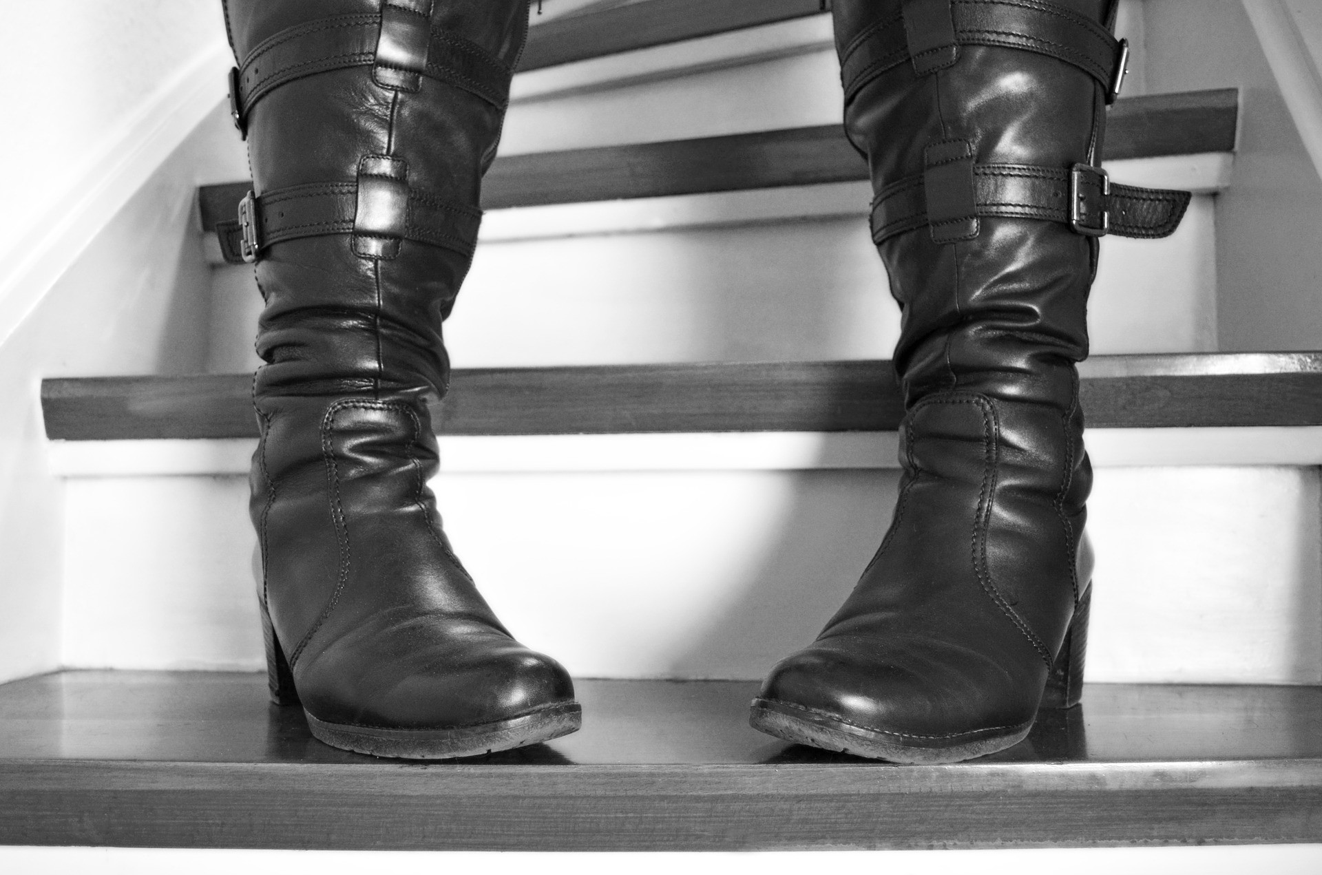 Close-up of someone in leather boots on stairs, toes pointed inwards
