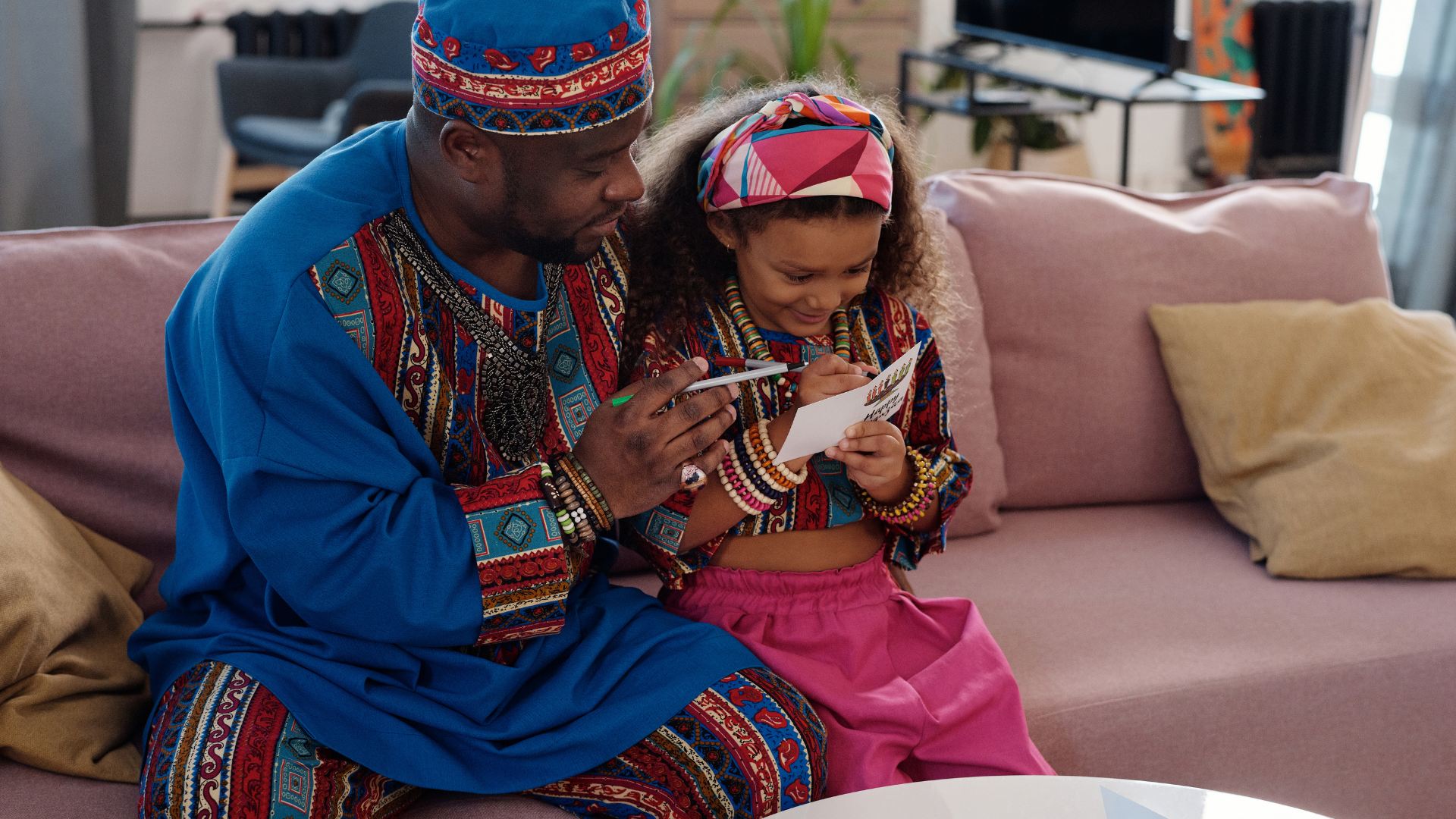 Photo of a man and his daughter writing on a paper