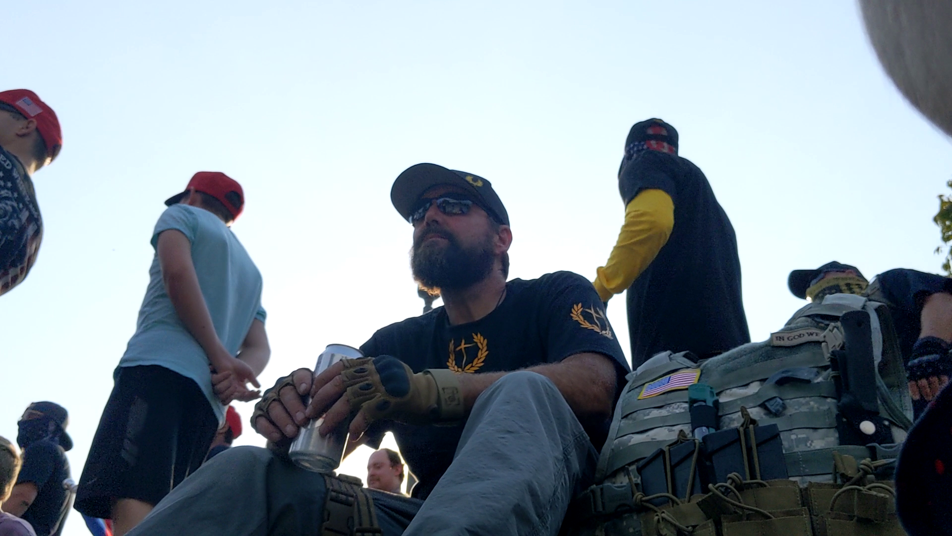 A man in a Proud Boy T-shirt drinks a beer next to body armor with visible AR-15 magazines and an American Flag patch