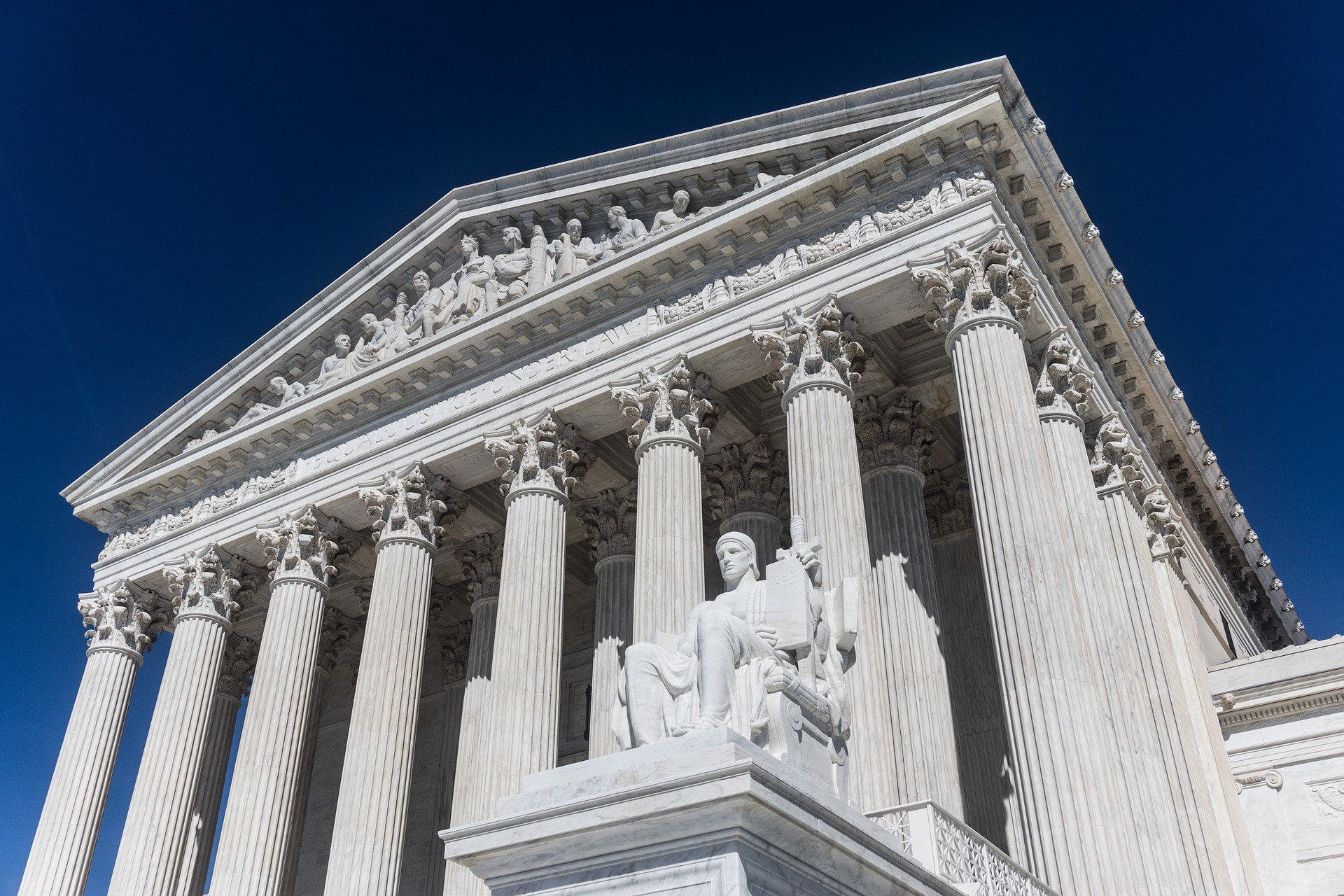 The United States Supreme Court building is photographed from below, showcasing its Greek architecture.