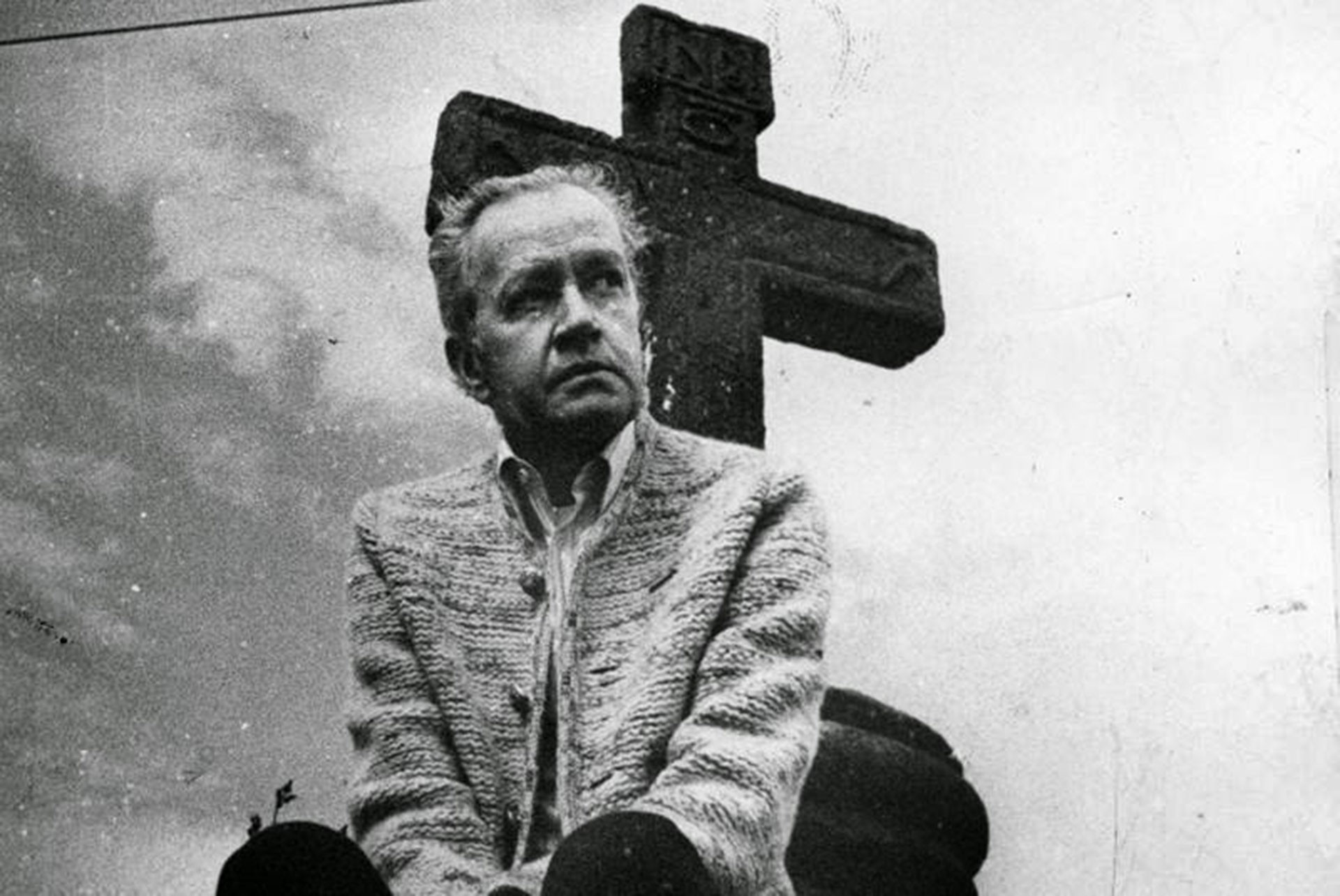 Black and white photograph of Juan Rulfo sitting in front of a stone cross.
