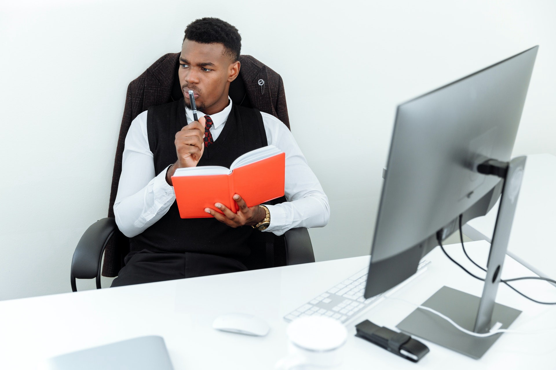 black guy thinking in his office